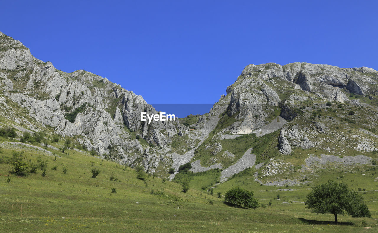 mountain, nature, clear sky, beauty in nature, tranquil scene, scenics, tranquility, landscape, blue, day, no people, outdoors, mountain range, sky, grass