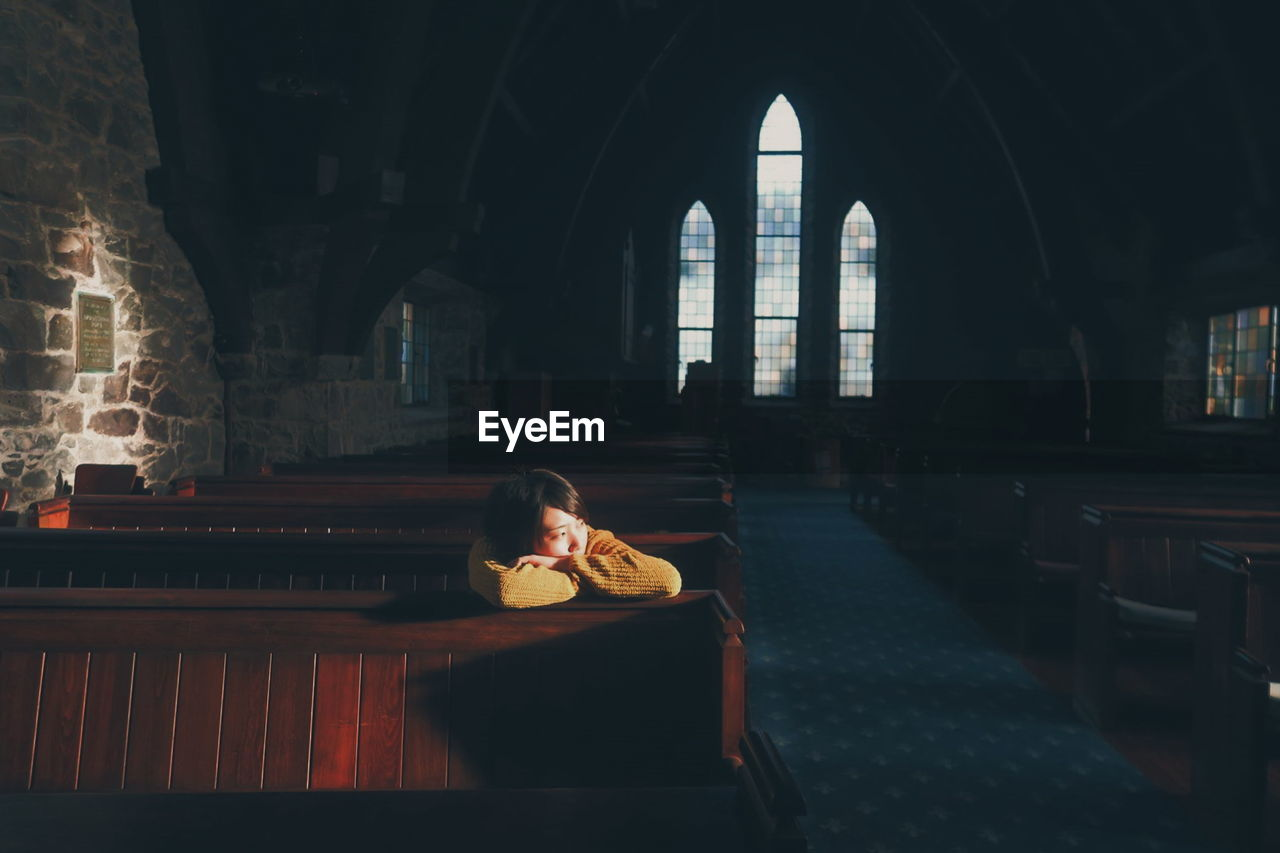 YOUNG WOMAN SITTING IN DARK CHRISTIAN CHURCH