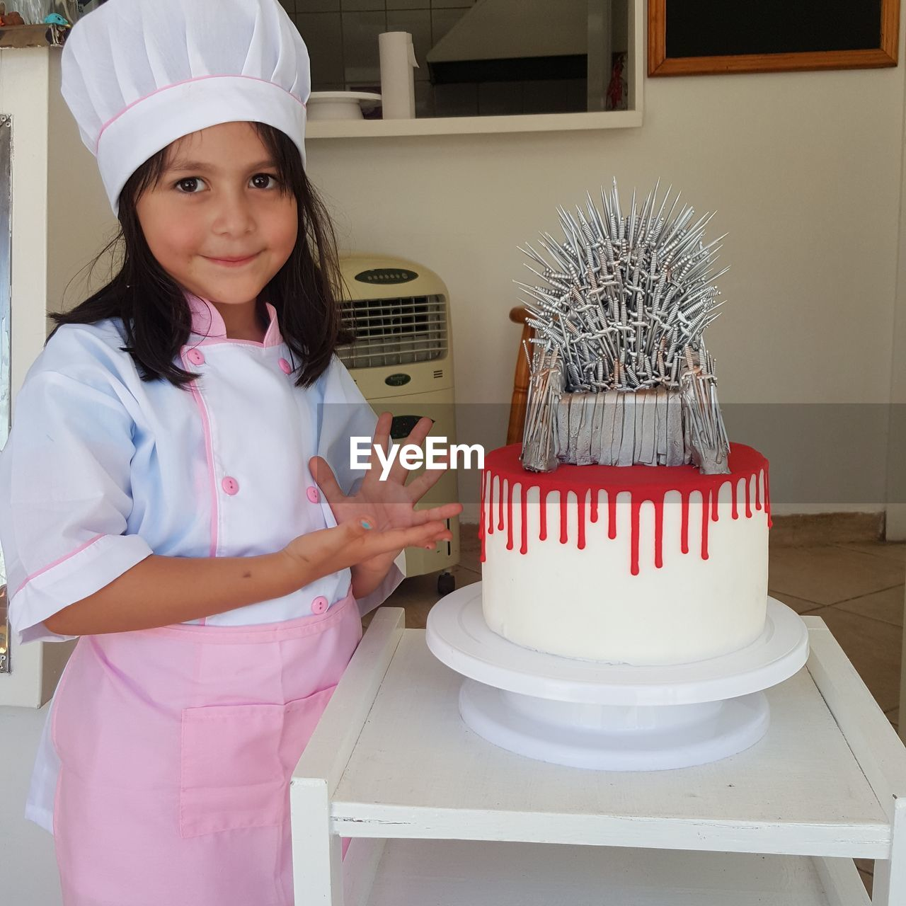 Portrait Of Girl In Chef White Standing By Cake At Home