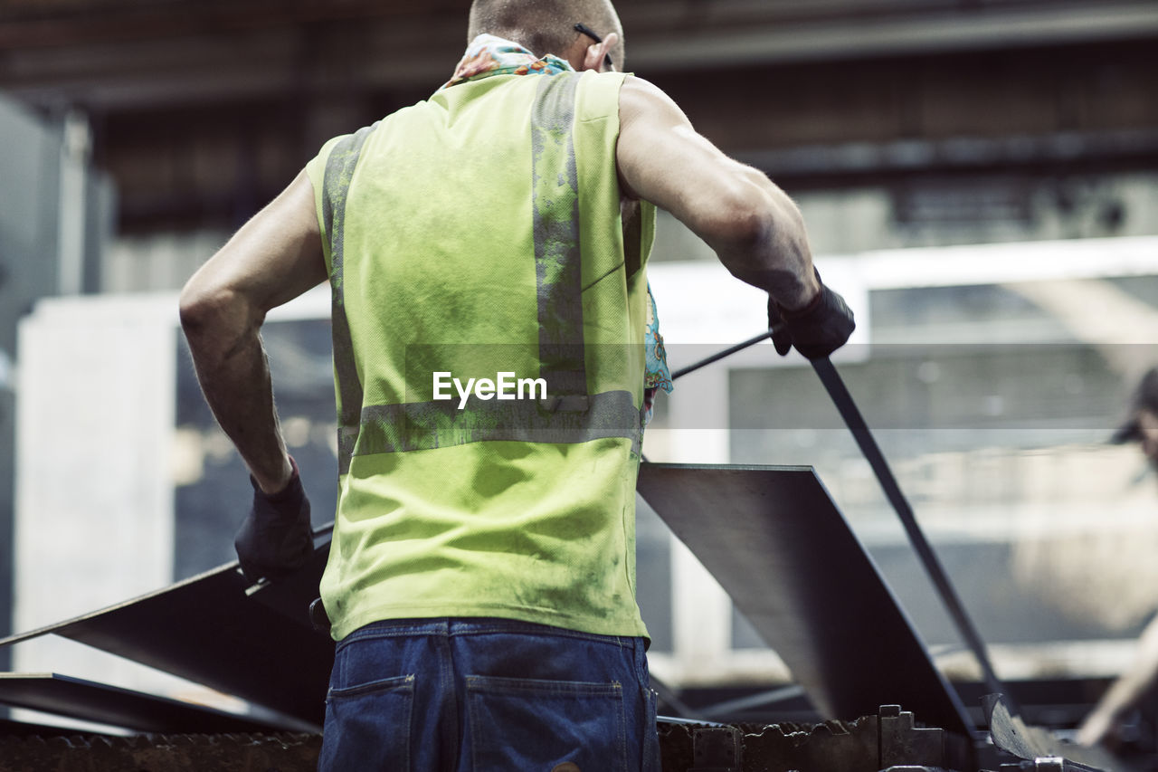 REAR VIEW OF MAN WORKING AT OFFICE