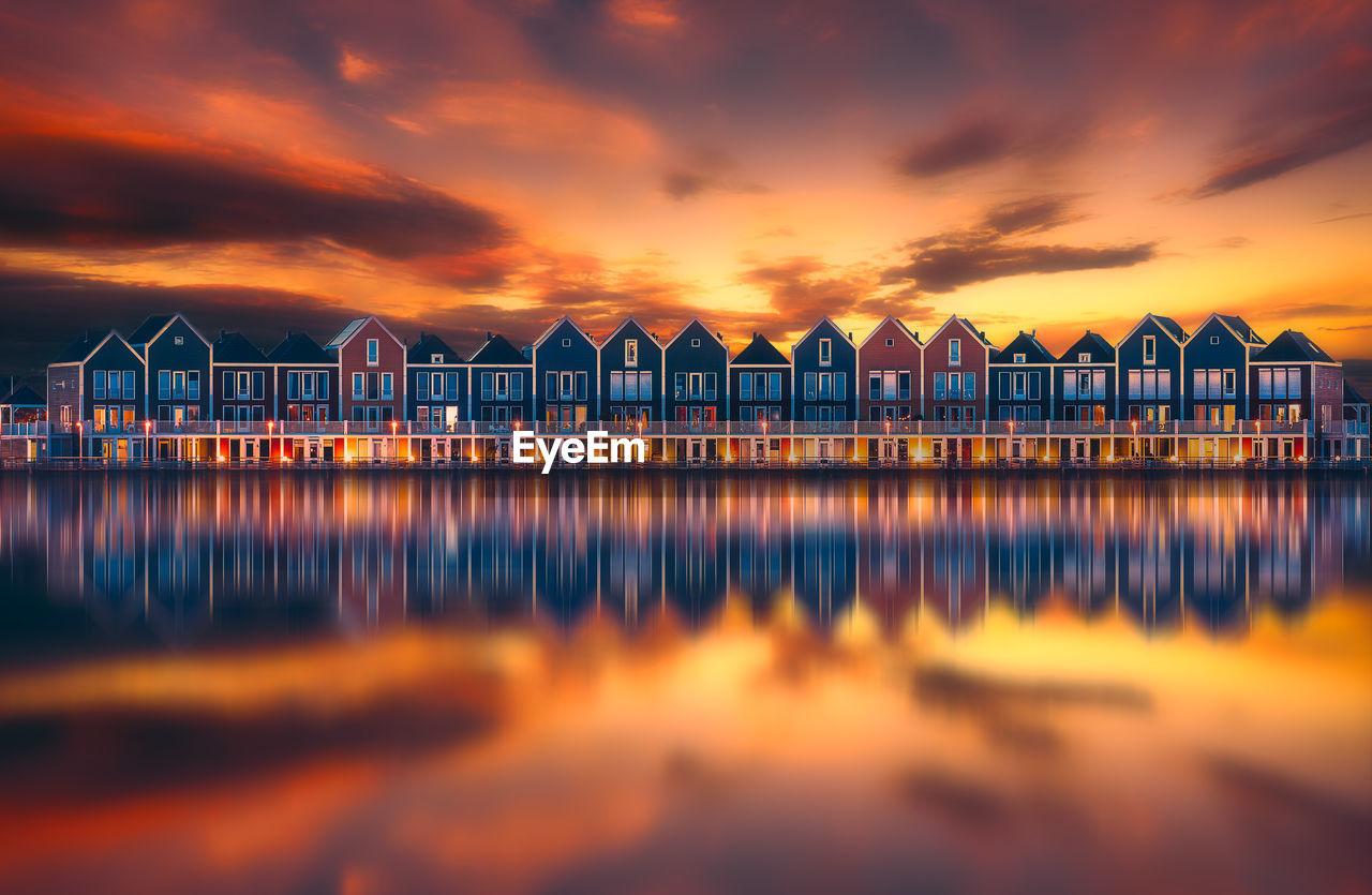 Houses Reflecting On Calm Lake Against Orange Sky During Sunset