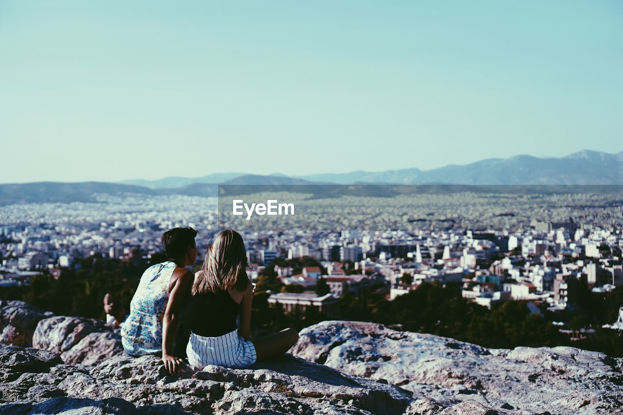 Rear View Of Women Looking At Cityscape While Sitting On Mountain Against Clear Sky