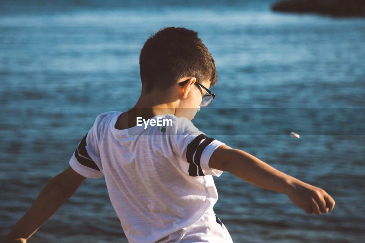 Boy standing at beach against sky