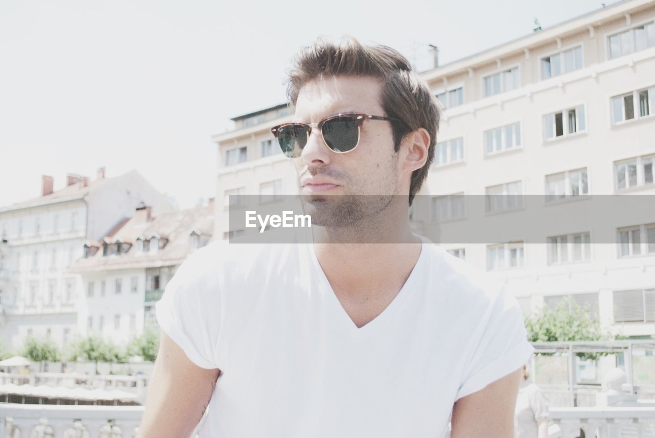 Young man in sunglass standing against building