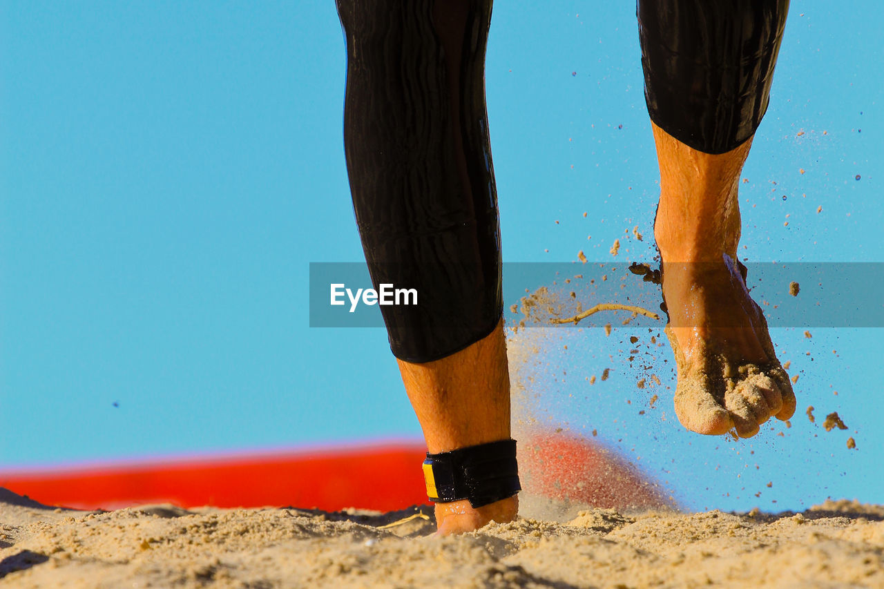 Low Section Of Person Walking On Sandy Beach