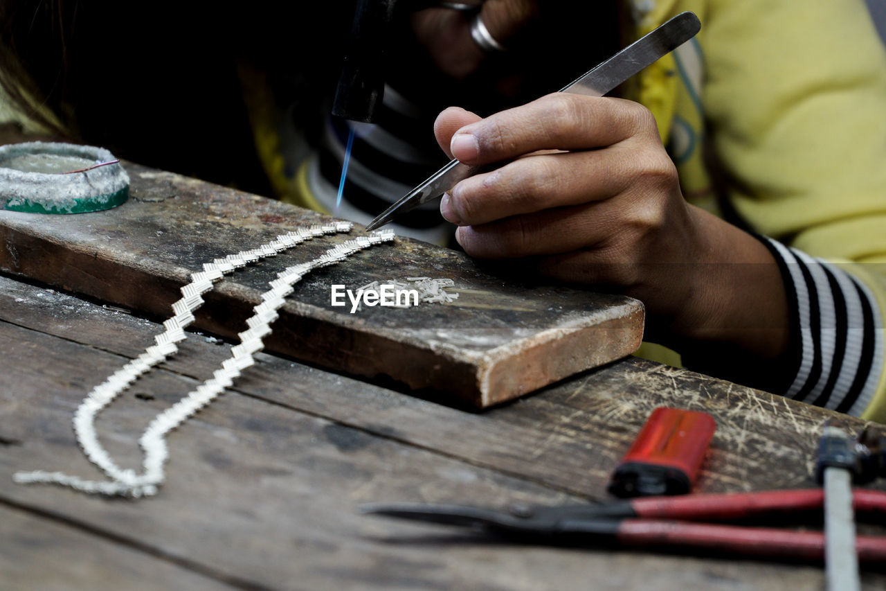 Close-up of person working on silver jewelery