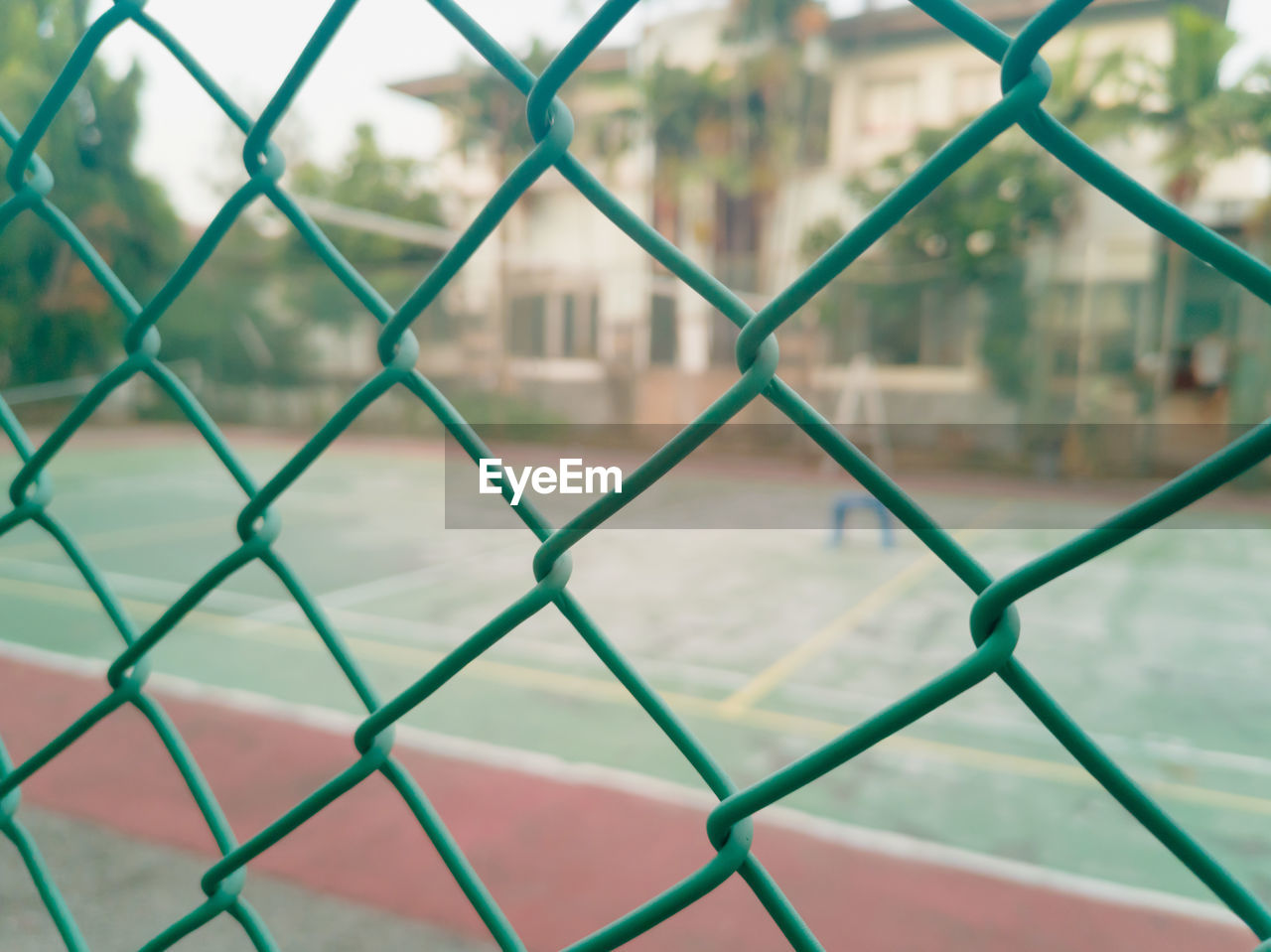 Wire fence with volleyball court on background