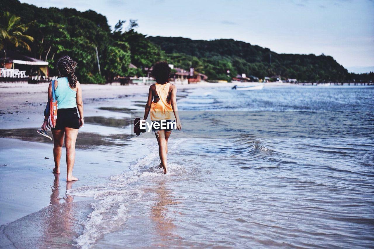 Rear View Of Women Walking On Shore