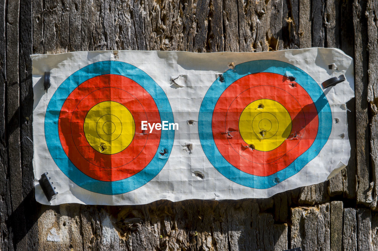 multi colored, no people, wood - material, circle, close-up, geometric shape, shape, sport, wall - building feature, sports target, pattern, day, outdoors, accuracy, tree, yellow, target shooting, directly above, flag, design