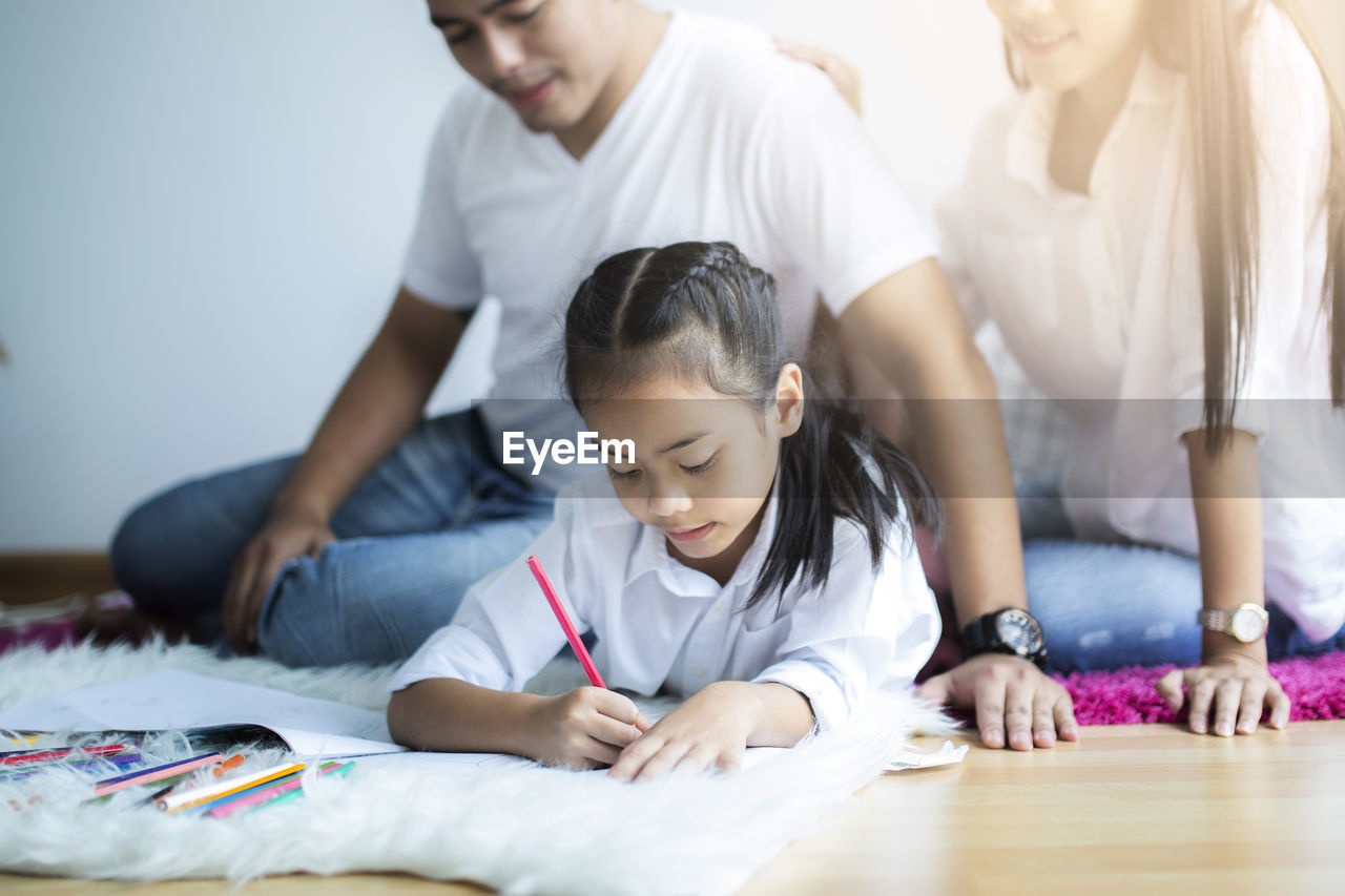 Girl doing drawing while lying on floor against parents in background at home