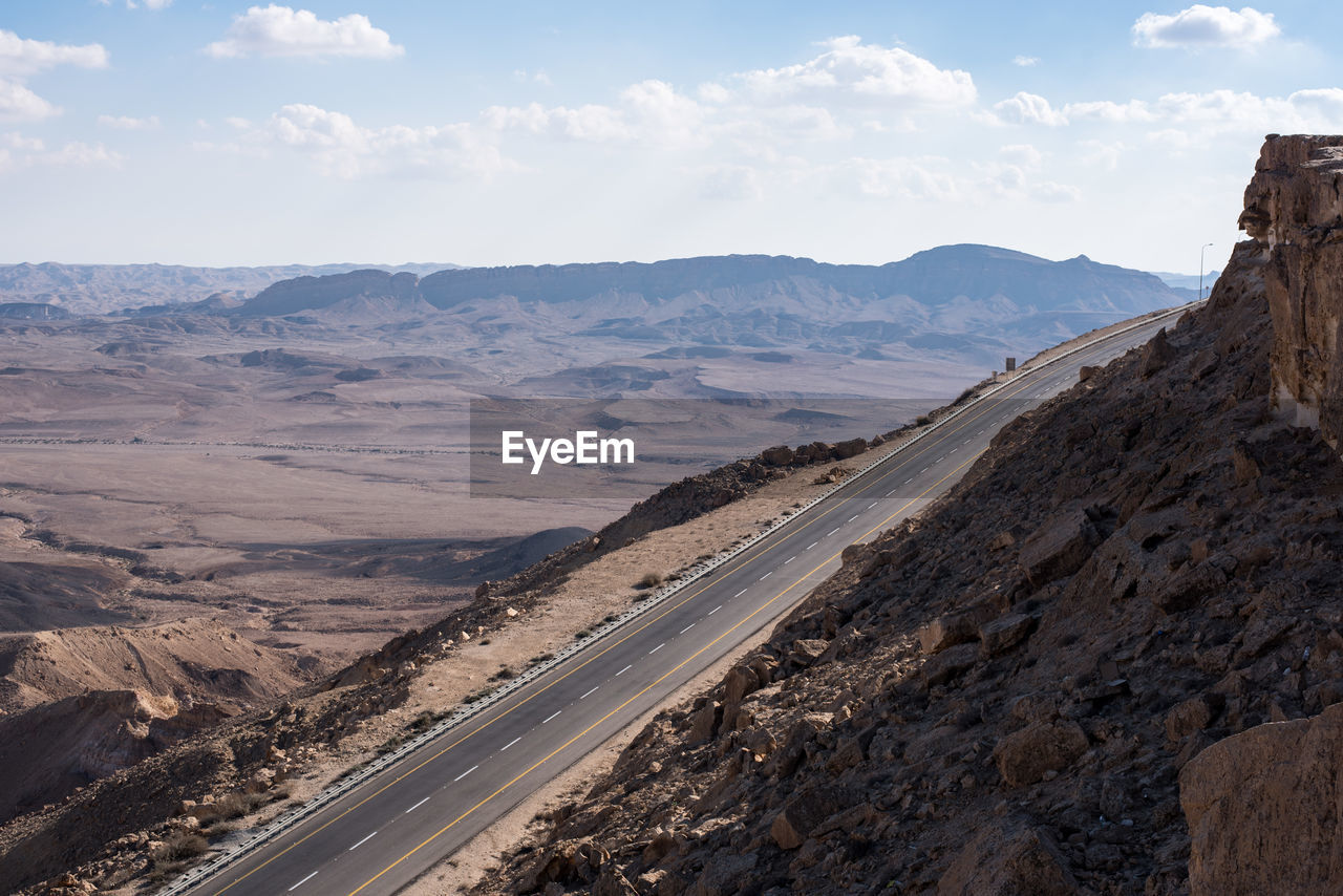 sky, mountain, scenics - nature, environment, landscape, cloud - sky, beauty in nature, road, nature, day, tranquil scene, mountain range, transportation, tranquility, non-urban scene, no people, desert, rock, land, rock formation, outdoors, arid climate, climate