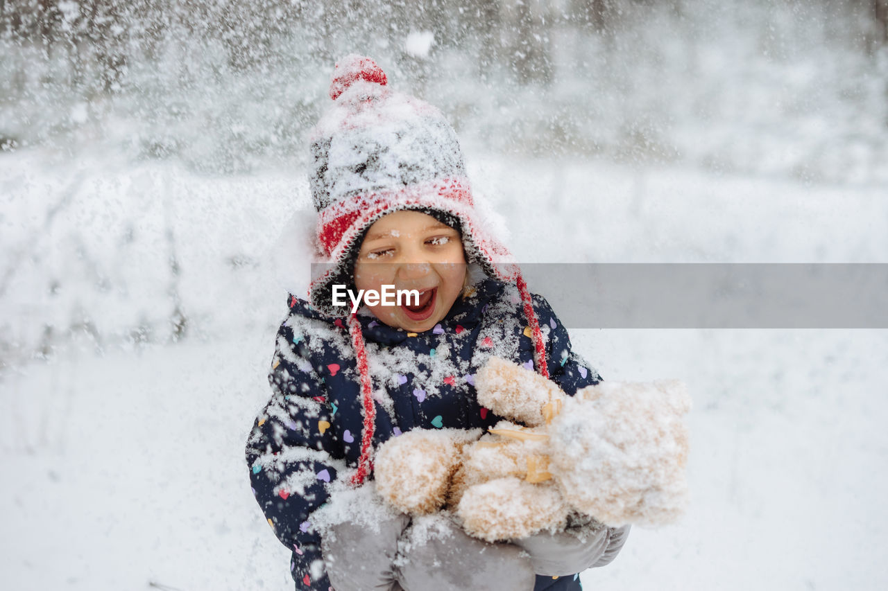 Happy child covered in snow playing outdoors.
