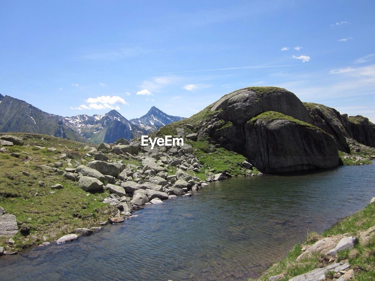Scenic view of stream by rocky mountains against sky