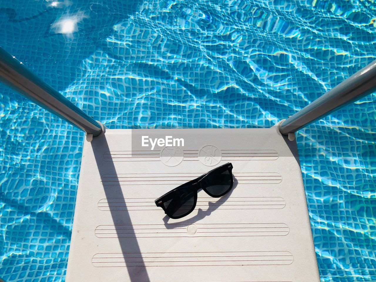 High angle view of sunglasses on ladder over swimming pool during sunny day