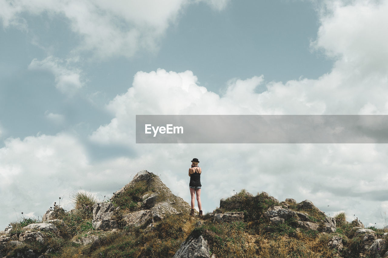 Rear View Of Woman Standing On Mountain Peak Against Cloudy Sky