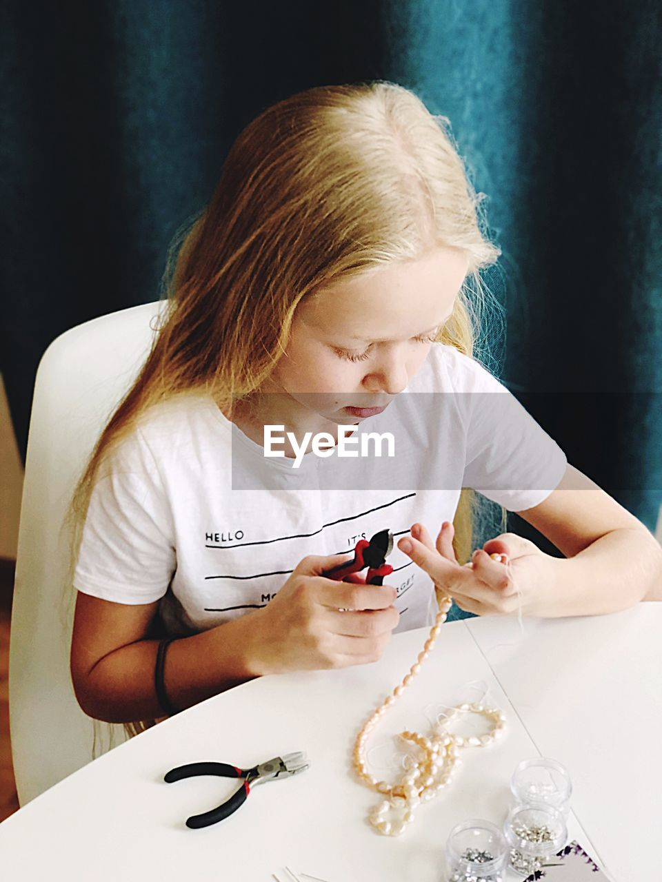 High Angle View Of Girl Making Bead Necklace At Table