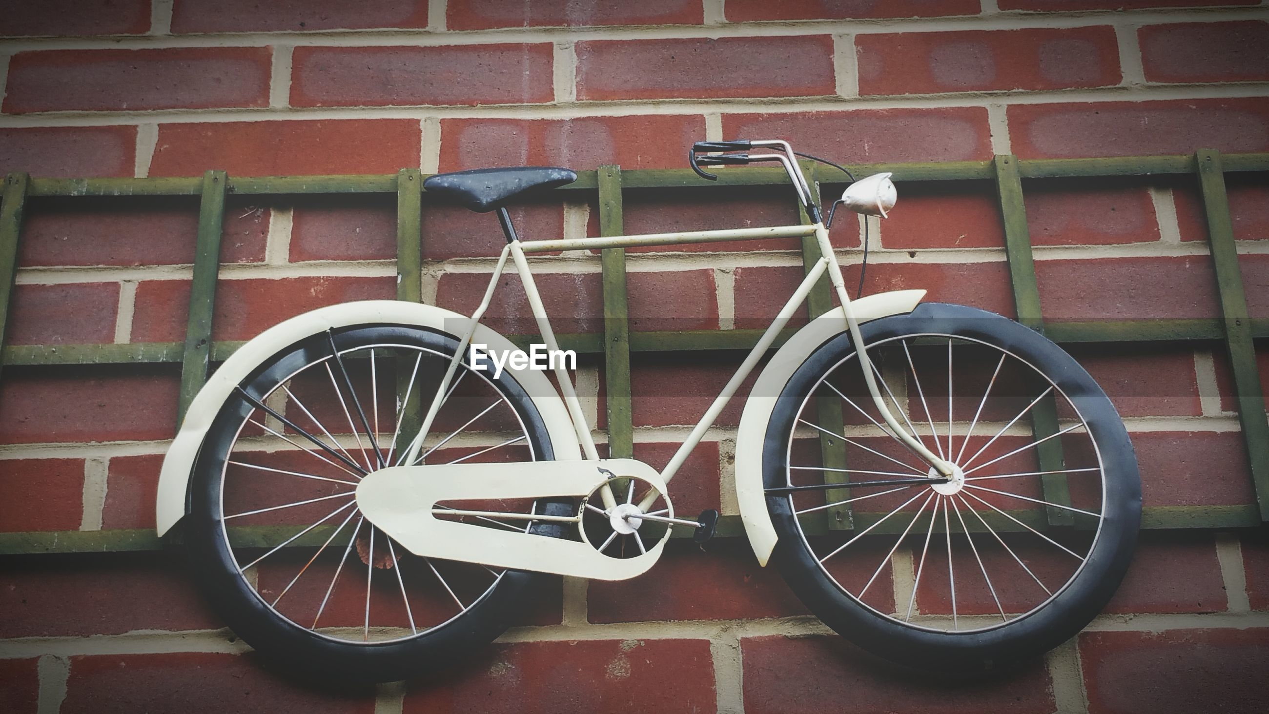 Low angle view of a bicycle against brick wall