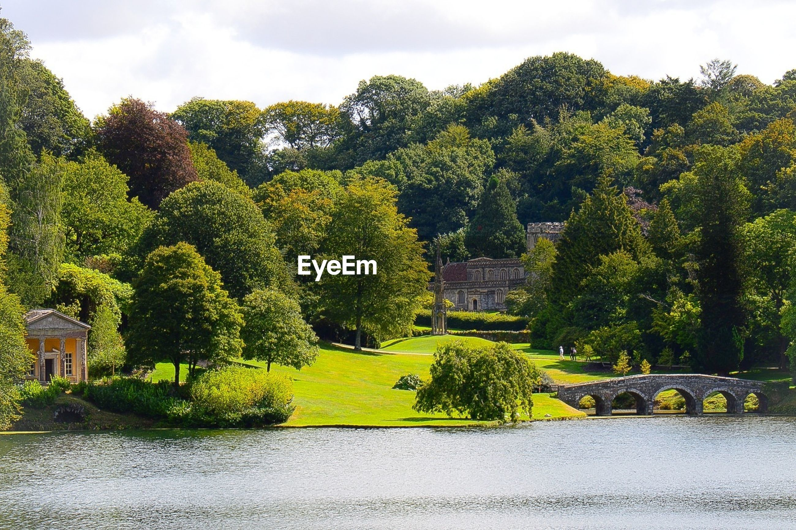 Scenic view of formal garden beside lake against cloudy sky