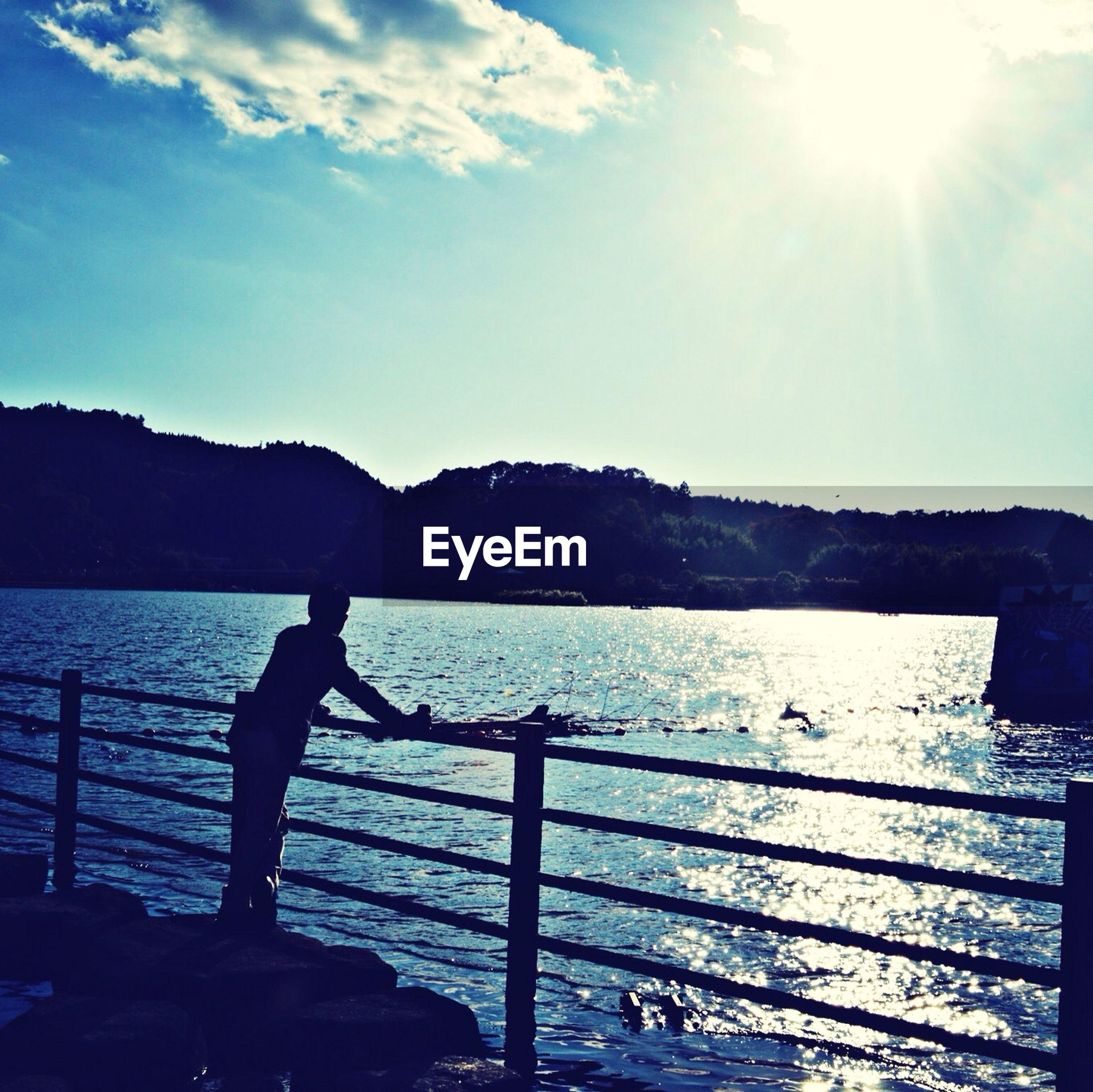 mountain, water, sun, mountain range, sunlight, sky, sunbeam, scenics, beauty in nature, tranquil scene, tranquility, sea, nature, nautical vessel, lake, lens flare, sunny, railing, outdoors, silhouette