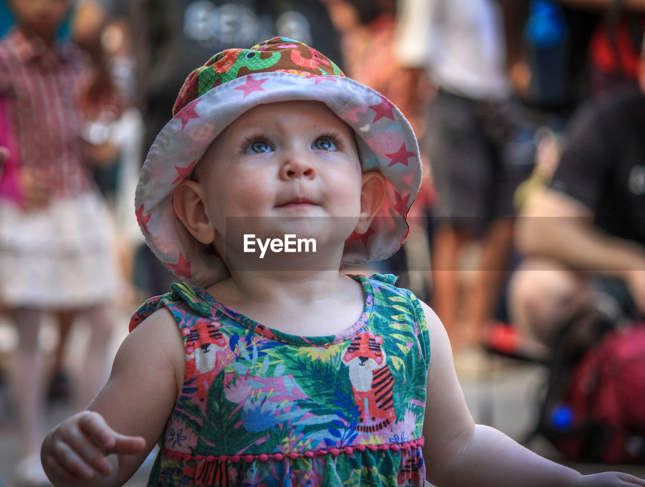 real people, childhood, innocence, focus on foreground, incidental people, cute, leisure activity, lifestyles, one person, elementary age, outdoors, day, cap, close-up, headshot, girls, headband, food, freshness