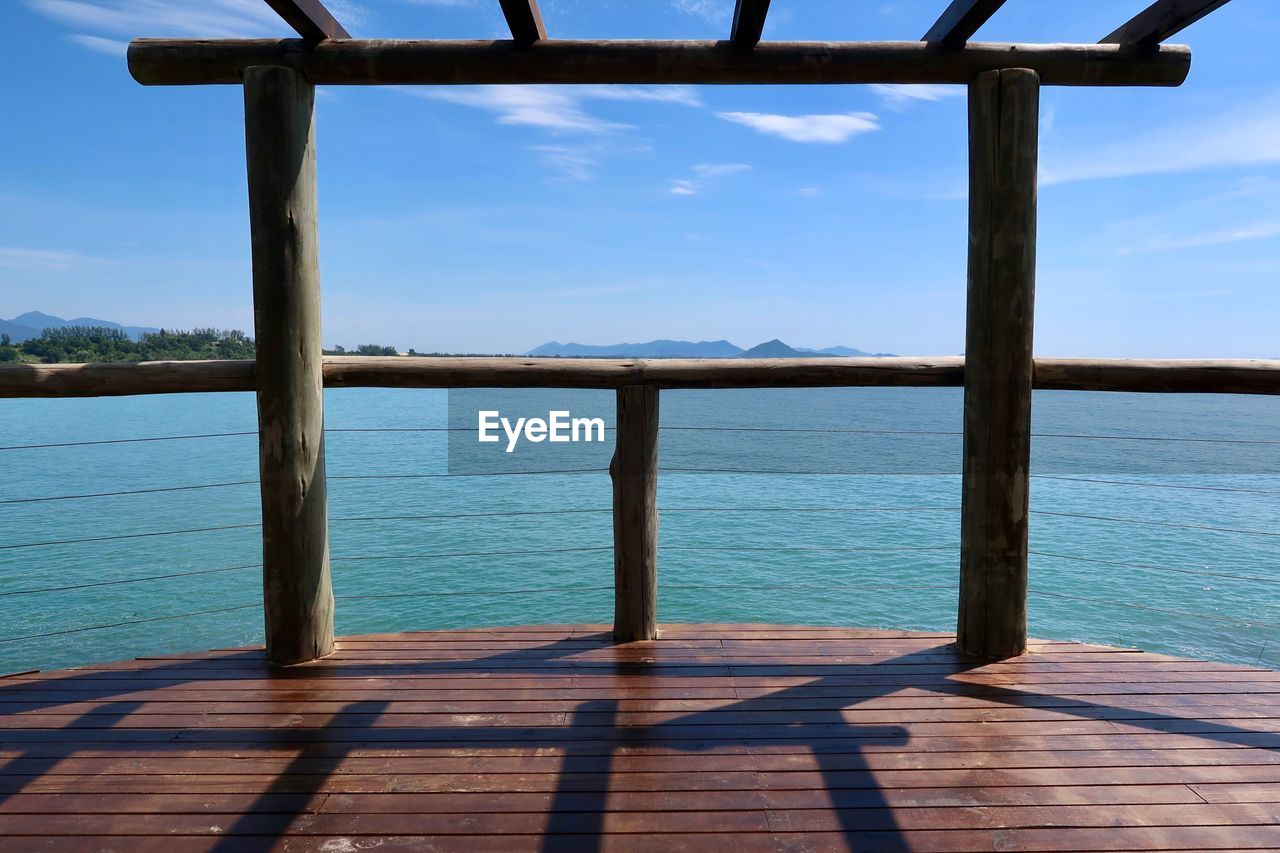 sky, water, sea, wood - material, nature, sunlight, day, beauty in nature, scenics - nature, blue, no people, shadow, railing, tranquil scene, tranquility, cloud - sky, outdoors, non-urban scene, idyllic, horizon over water, wood