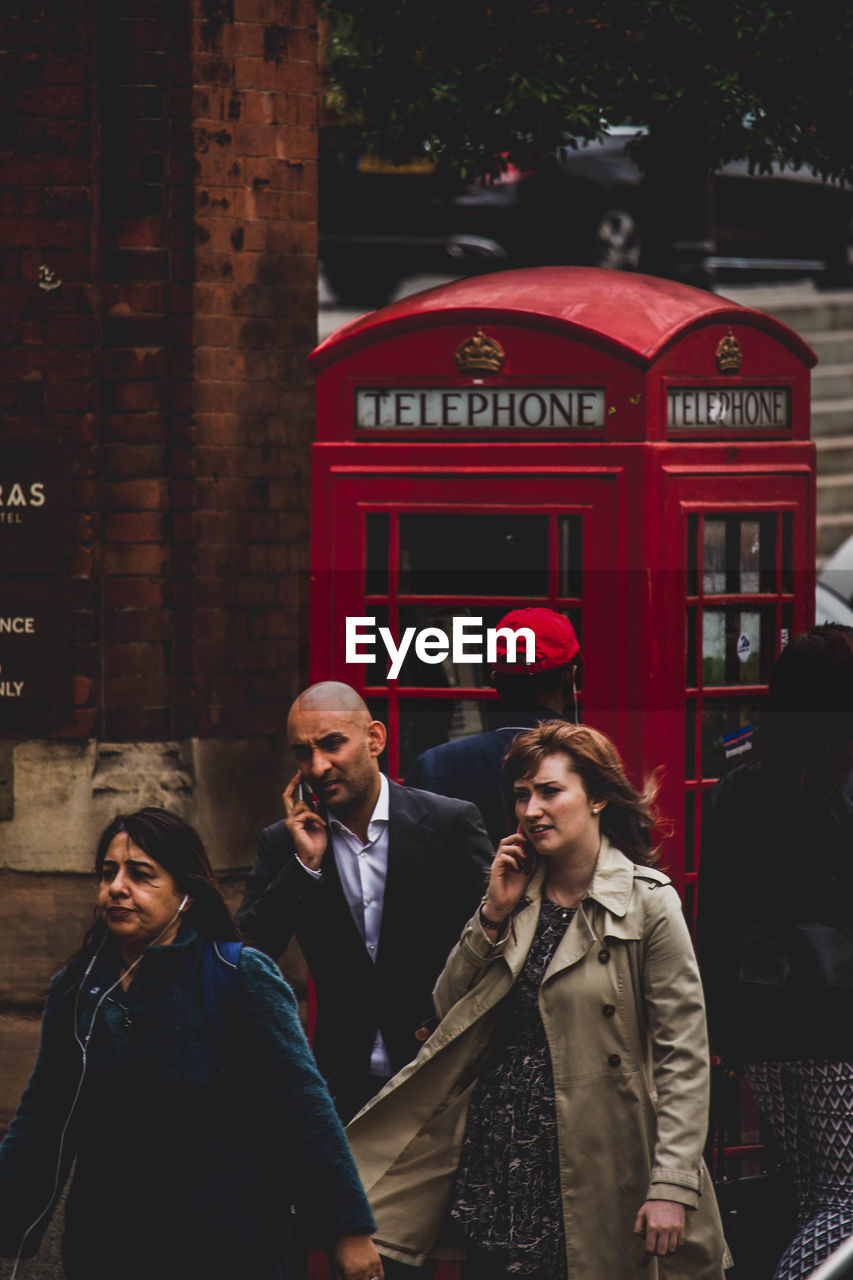 communication, red, text, real people, street, telephone booth, architecture, building exterior, built structure, outdoors, lifestyles, city, day, pay phone