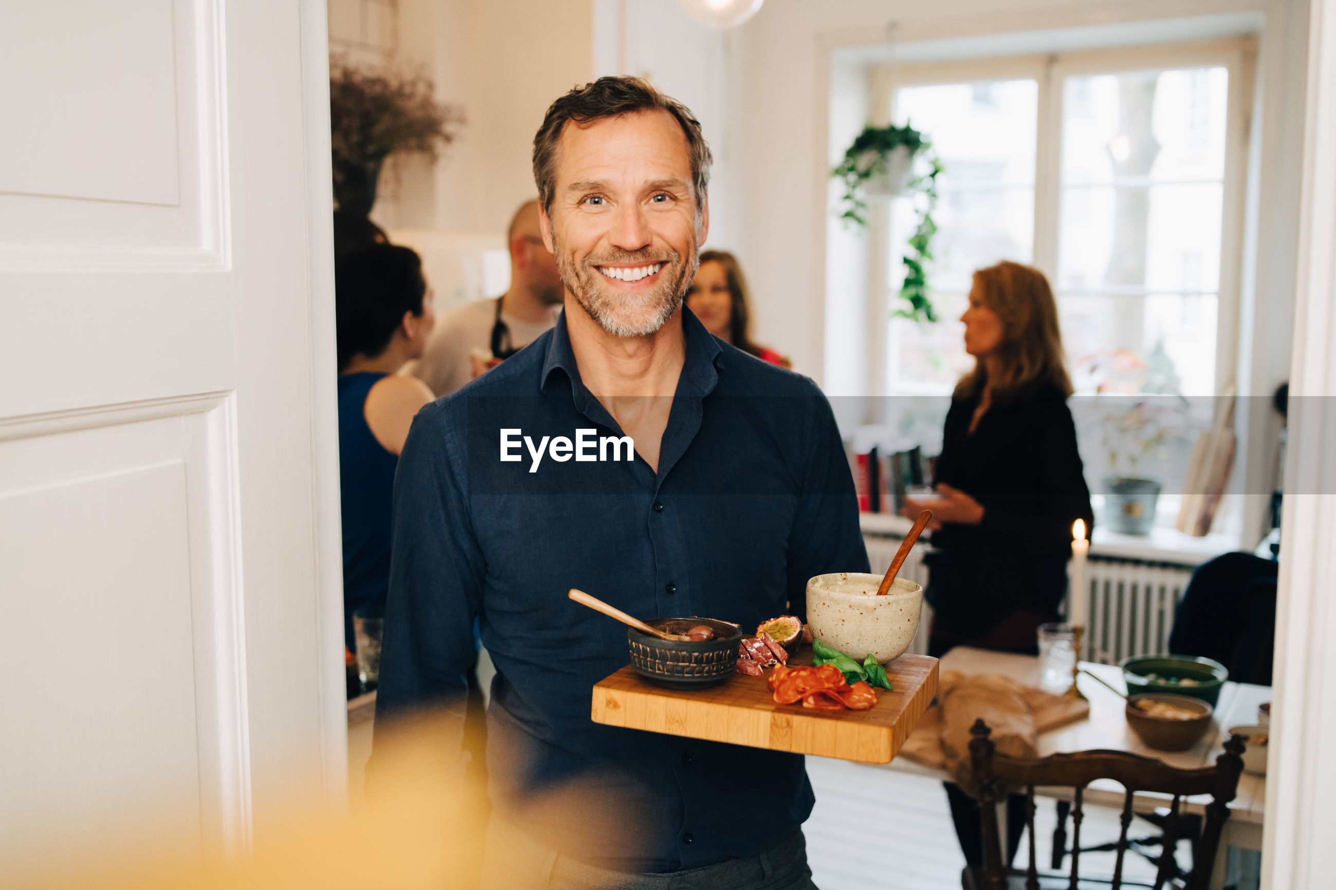 Portrait of smiling mature man holding food in serving tray while standing against friends at party