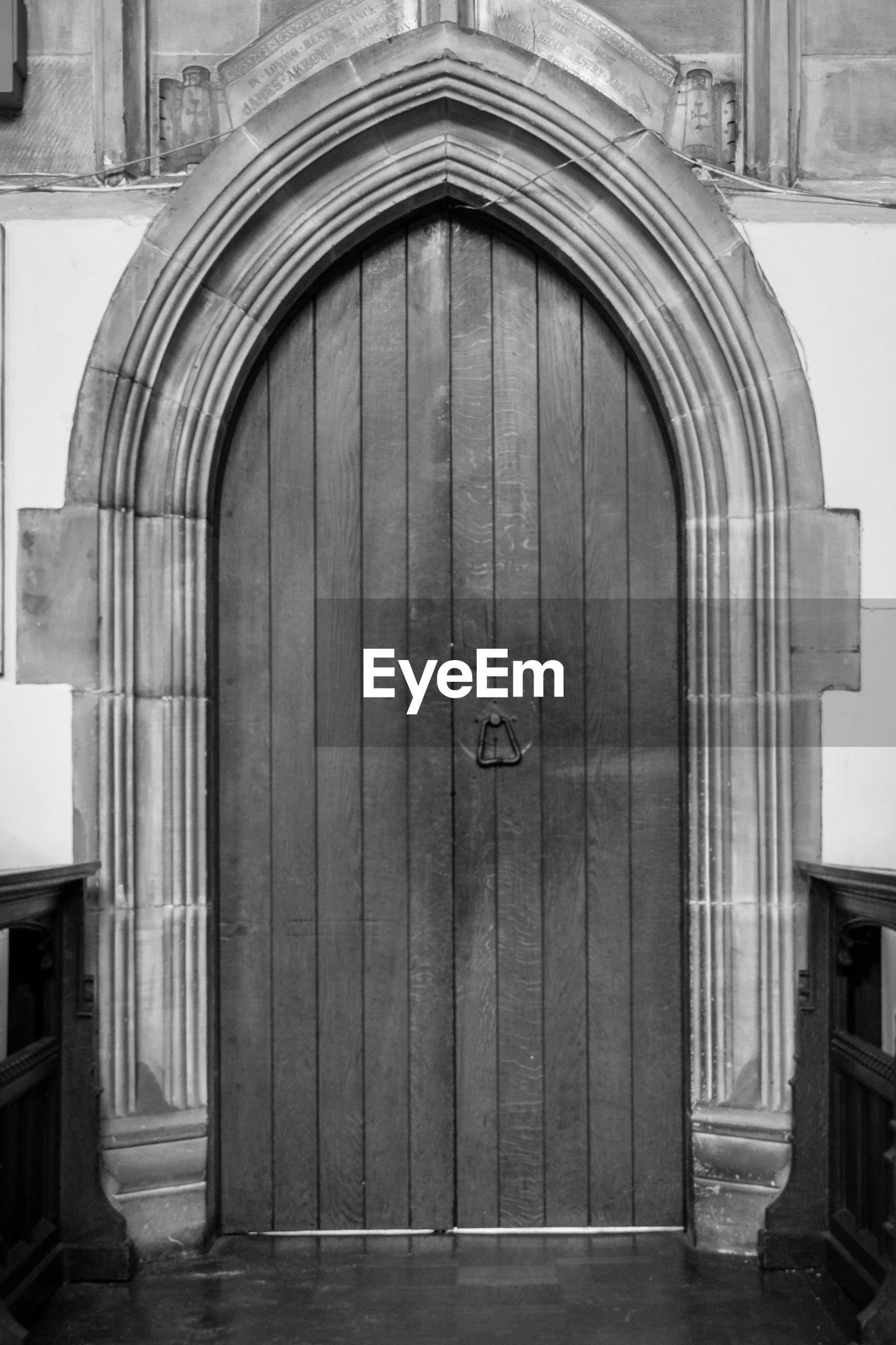 CLOSED DOOR OF BUILDING AGAINST CHURCH