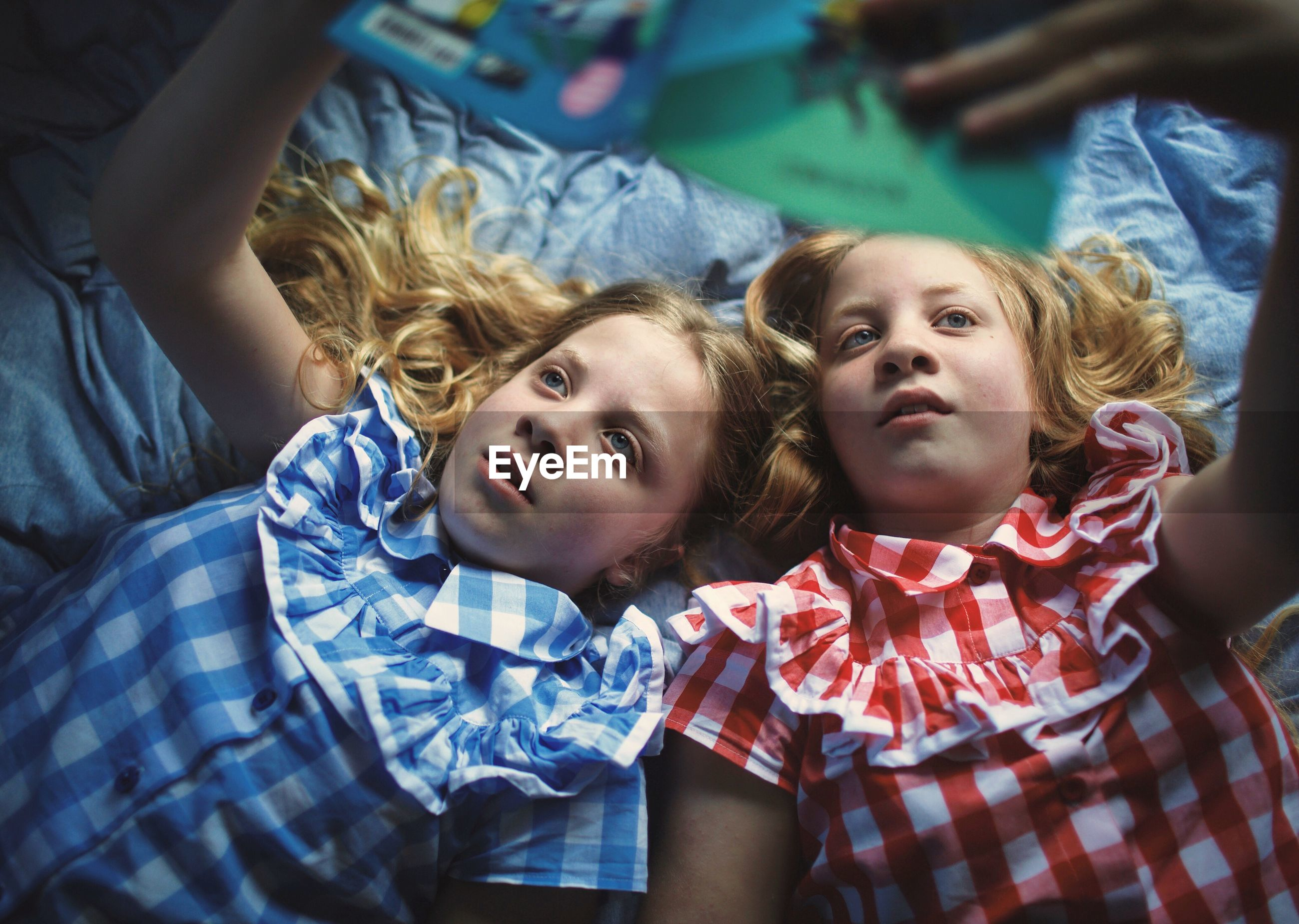 Cute sisters reading book on bed at home