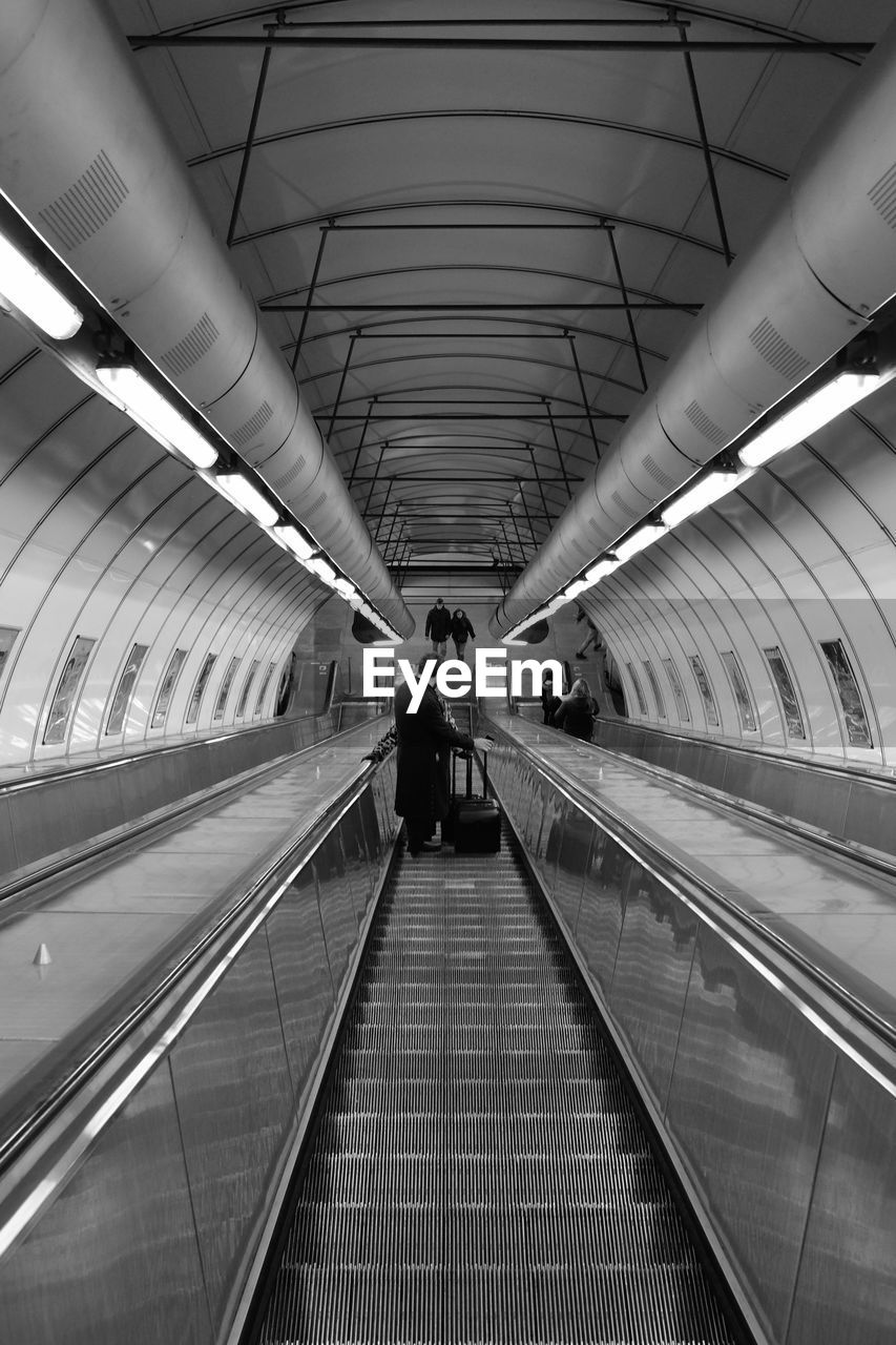 illuminated, indoors, direction, architecture, transportation, convenience, the way forward, moving walkway, modern, men, technology, ceiling, railing, built structure, incidental people, travel, diminishing perspective, futuristic, real people, subway station