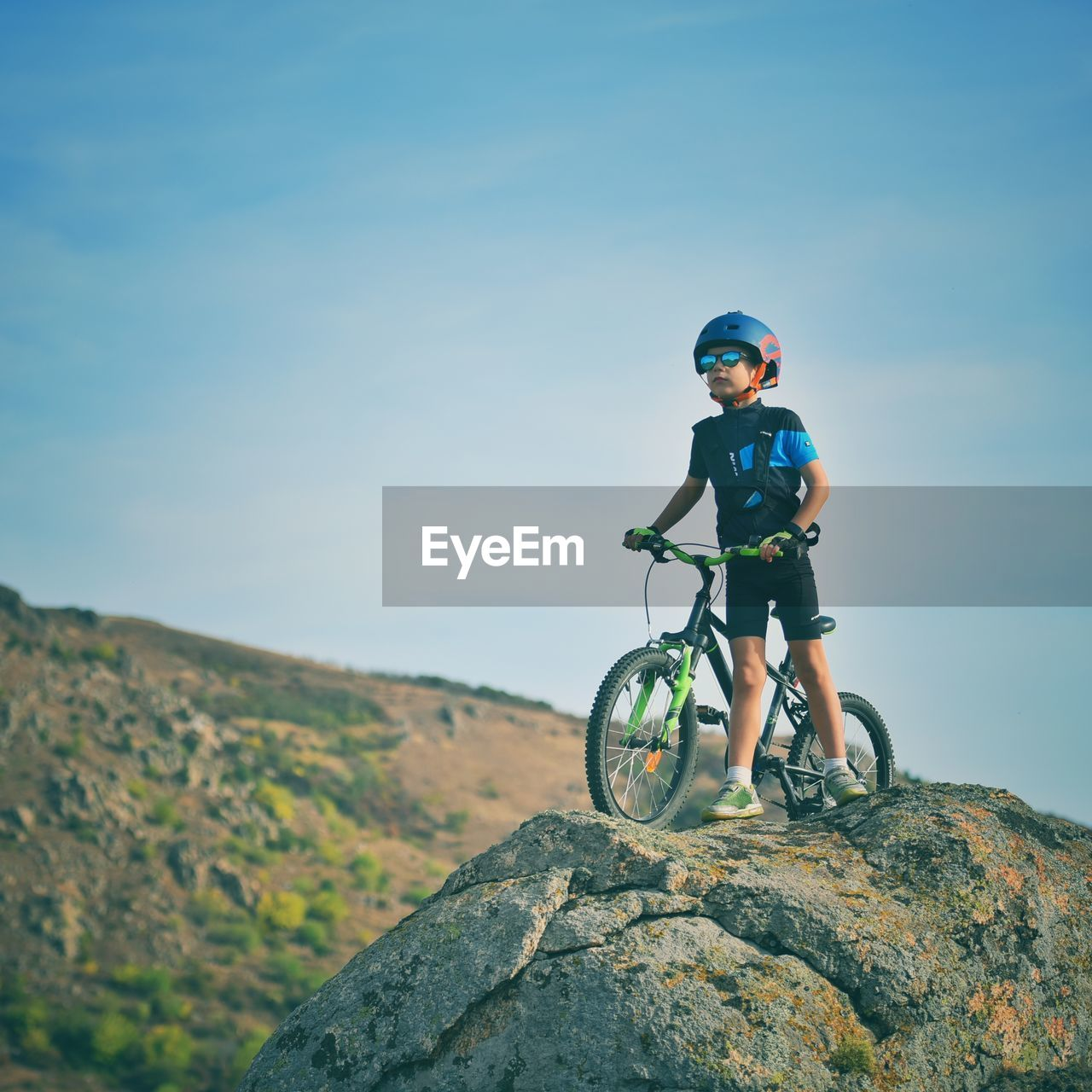 adventure, one person, leisure activity, rock, sky, helmet, rock - object, lifestyles, solid, mountain, activity, real people, sport, nature, day, full length, extreme sports, men, headwear, outdoors