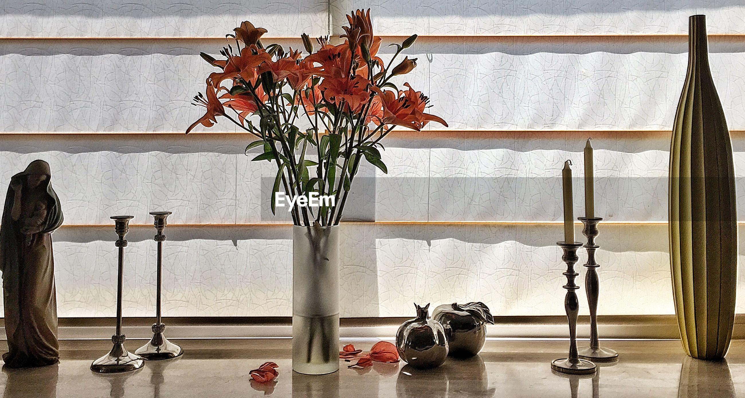 Flower vase amidst candlestick holder on table