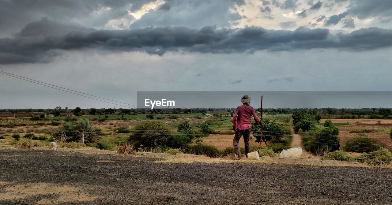 REAR VIEW OF MAN WALKING ON ROAD AMIDST LAND