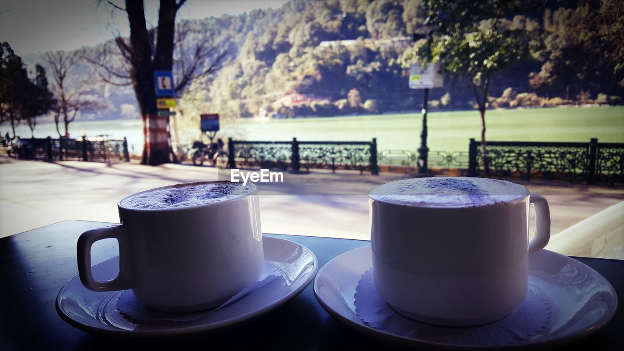coffee cup, coffee - drink, drink, food and drink, refreshment, table, saucer, focus on foreground, close-up, day, tree, no people, plate, outdoors, cafe, freshness, frothy drink, water, nature