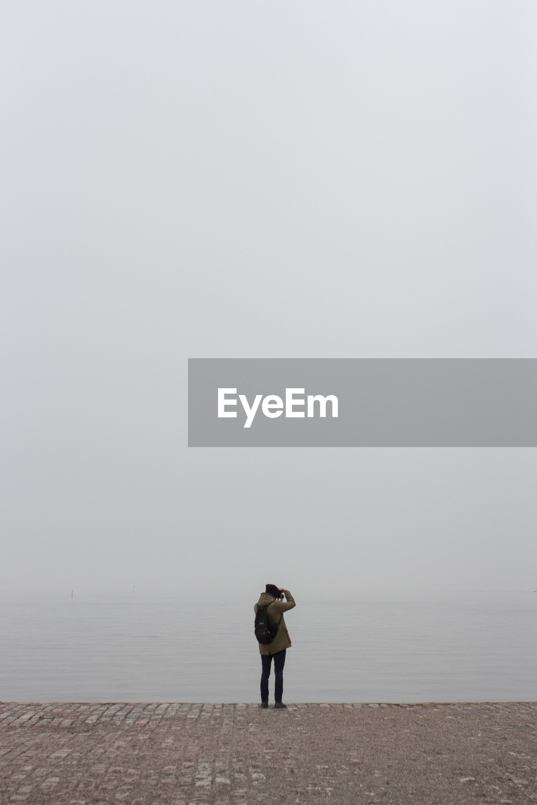 REAR VIEW OF MAN STANDING ON SEA SHORE AGAINST SKY