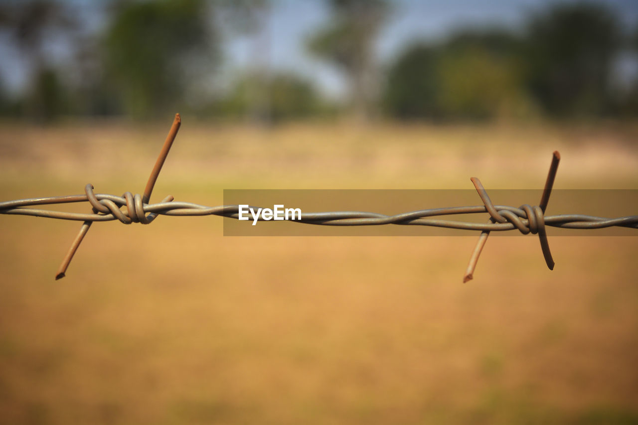 Close-up of barbed wire fence on field