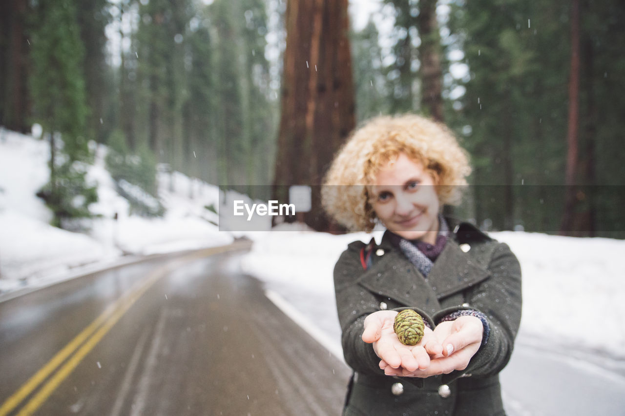 Portrait Of Smiling Young Woman Holding Pine Cone