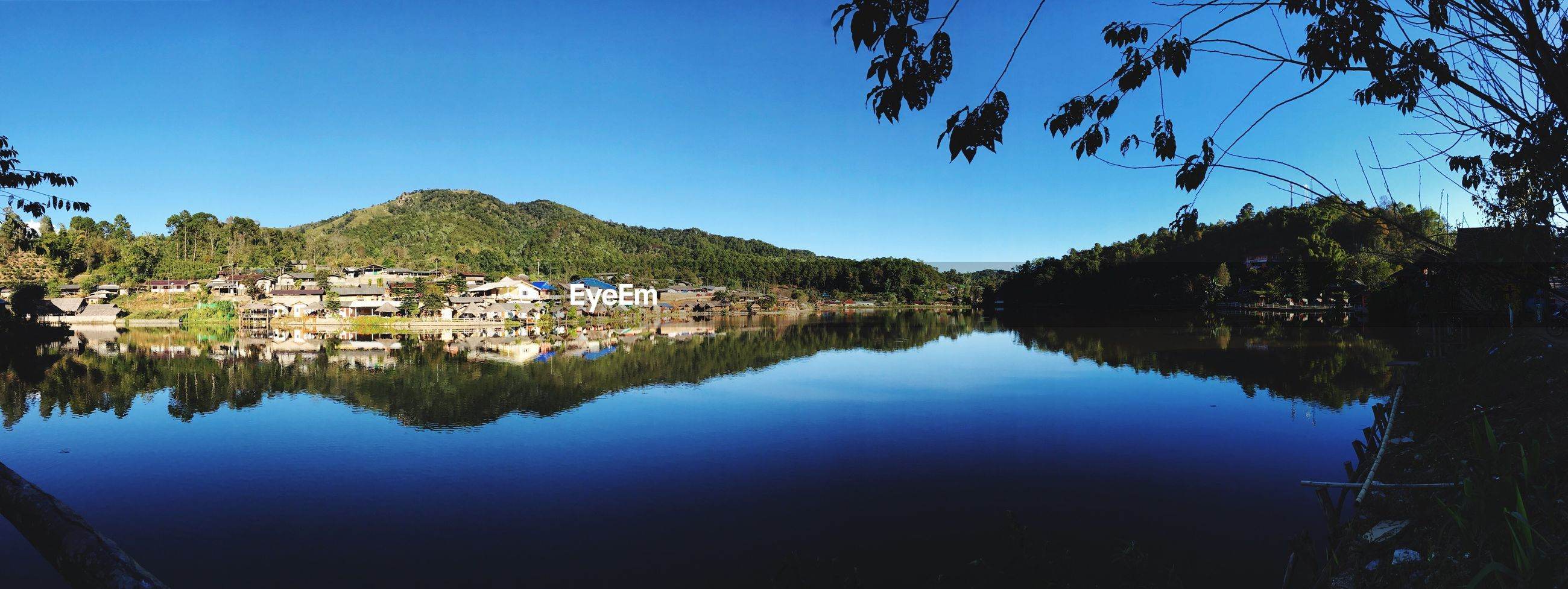 SCENIC VIEW OF LAKE BY TOWN AGAINST CLEAR SKY