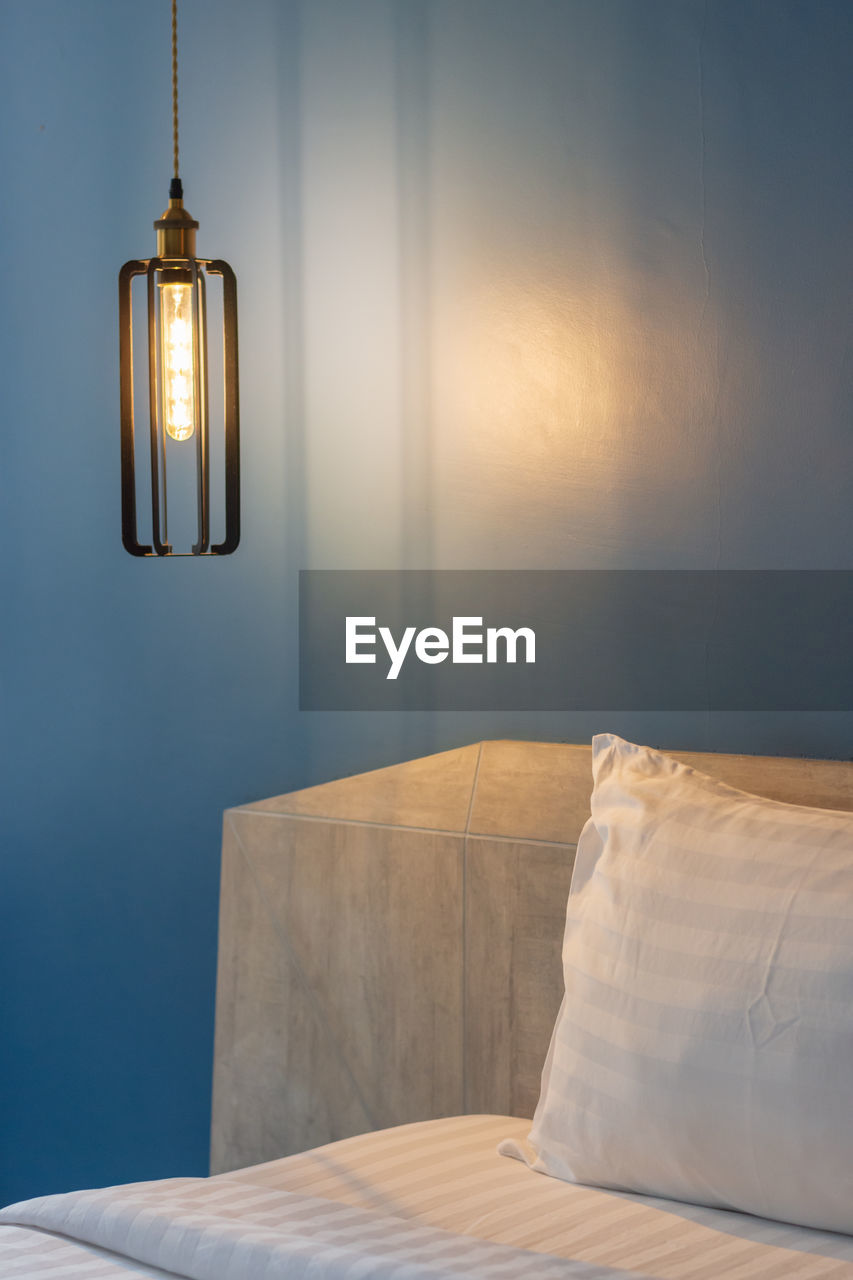 lighting equipment, indoors, furniture, bed, wall - building feature, illuminated, no people, bedroom, domestic room, home interior, light, electric lamp, absence, architecture, built structure, hanging, pillow, glowing, electric light, building, luxury