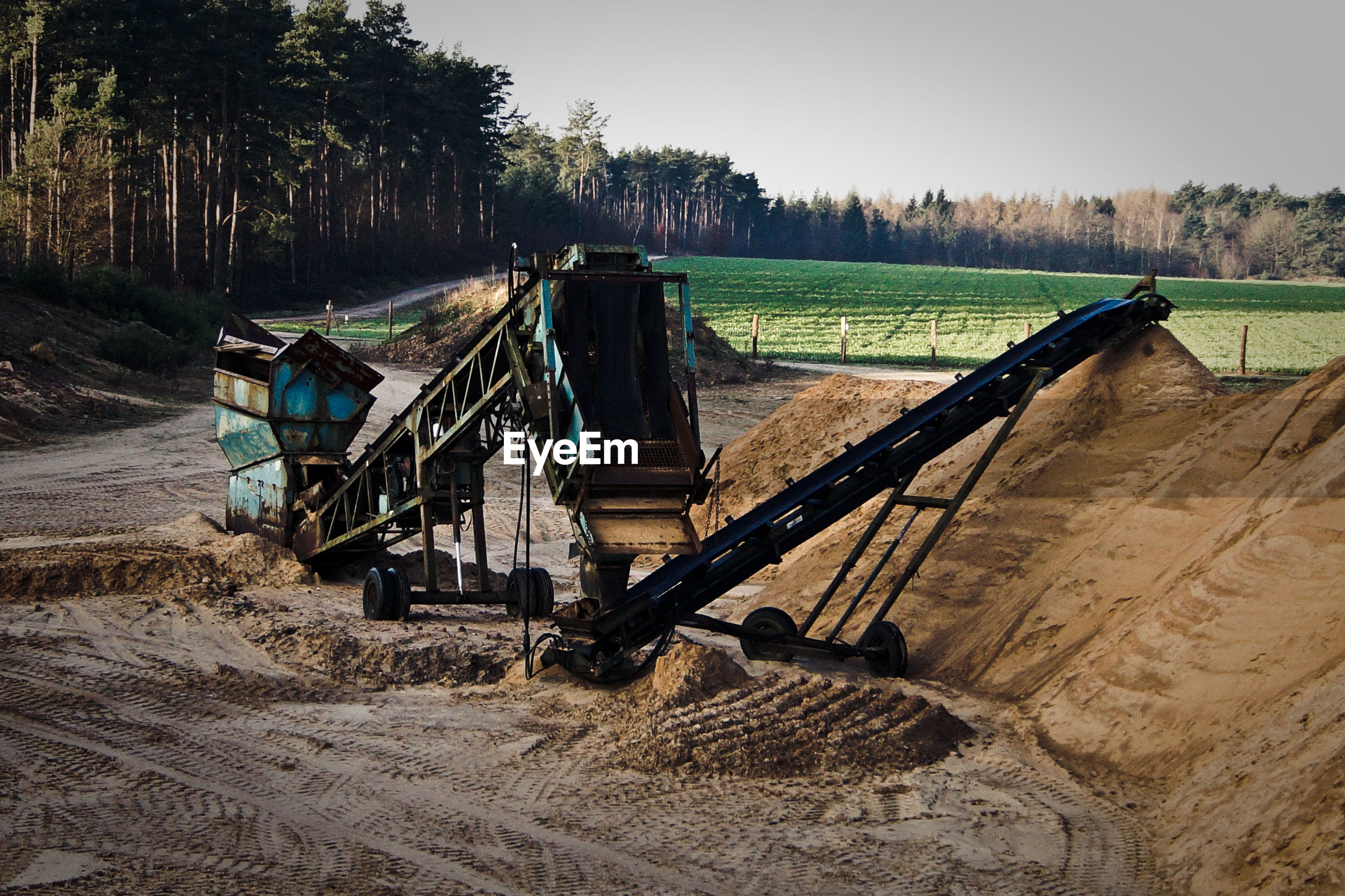 High angle view of construction machinery by sand against field