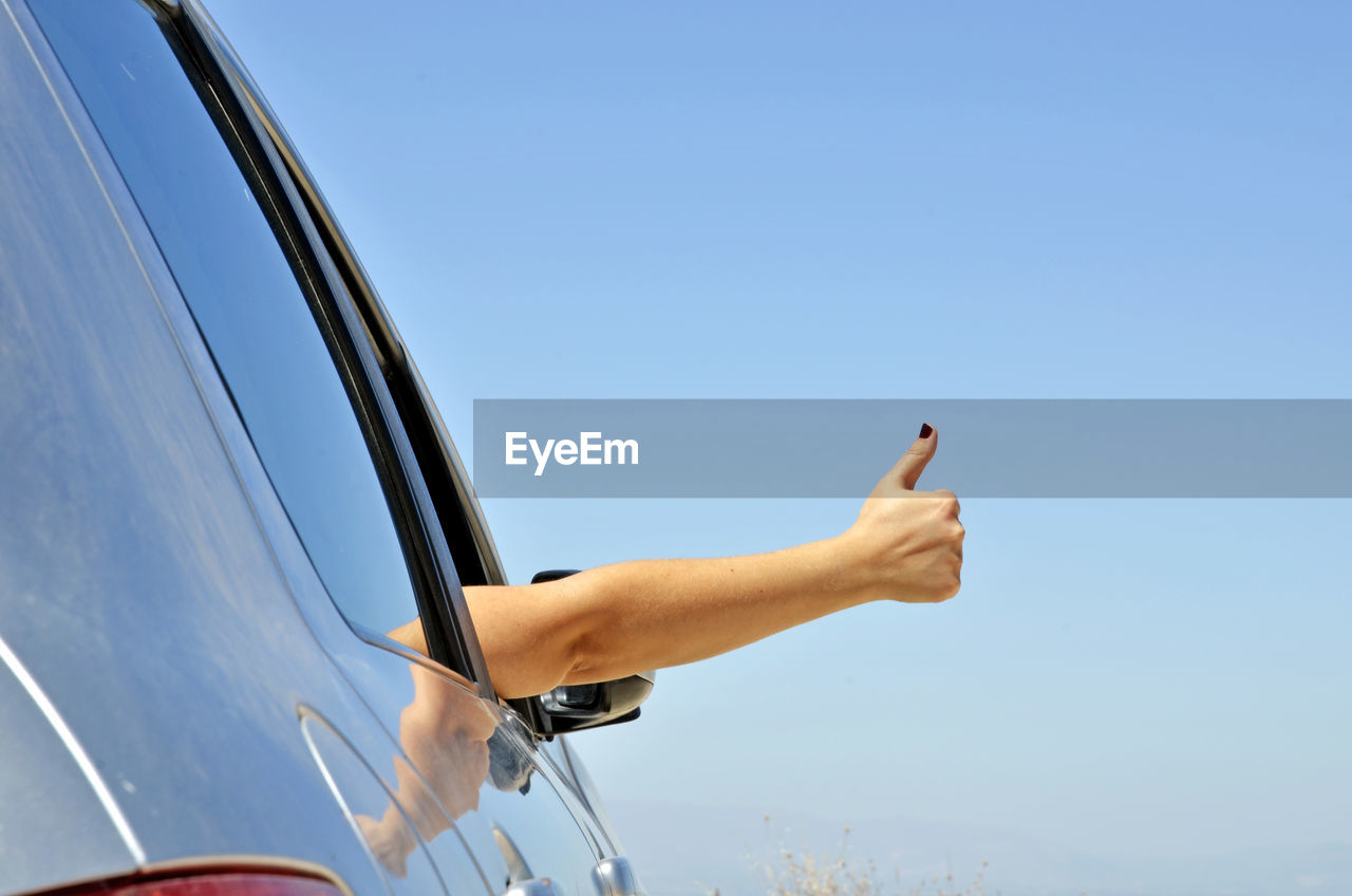 Cropped hand of woman gesturing in car window against blue sky