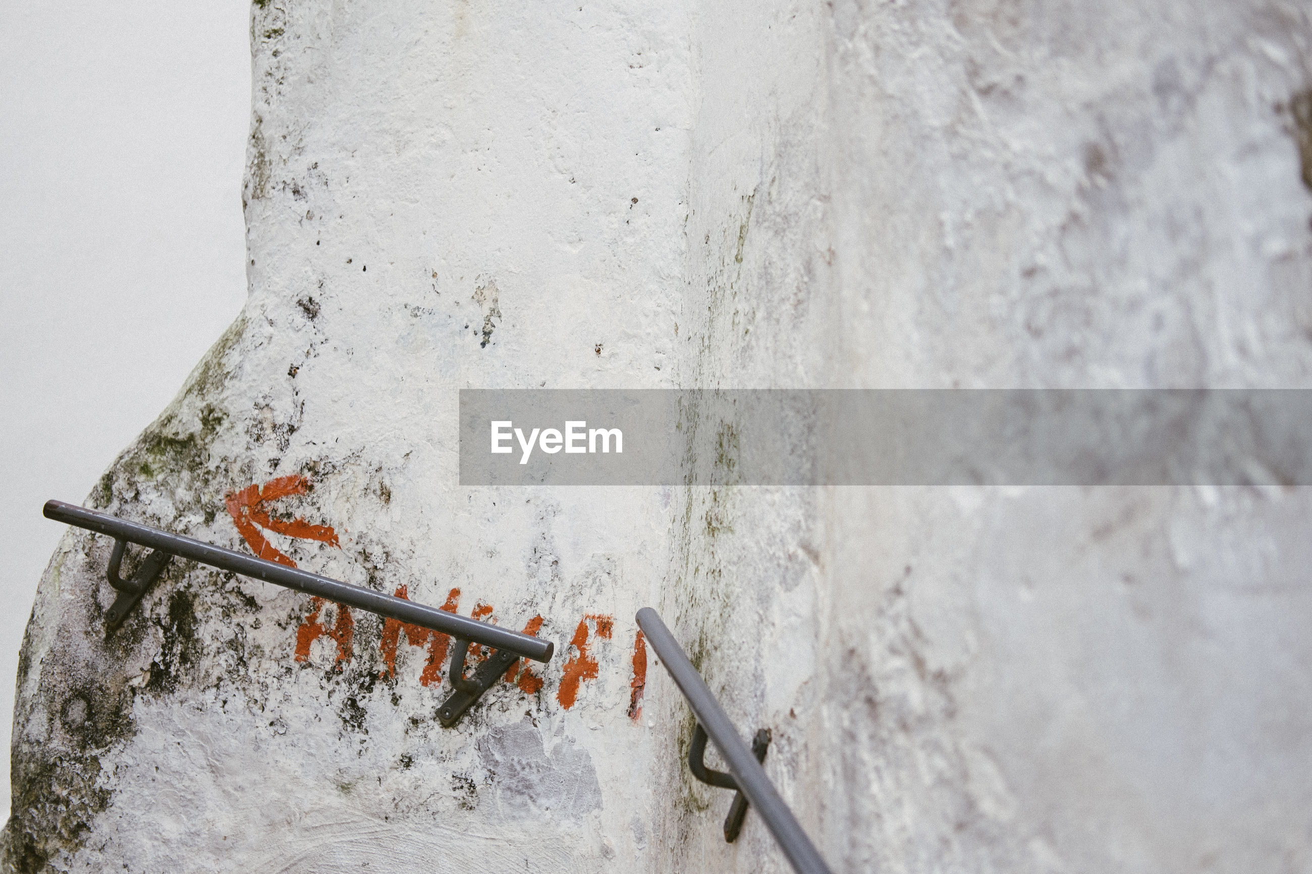 HIGH ANGLE VIEW OF RUSTY RAILING AGAINST WALL