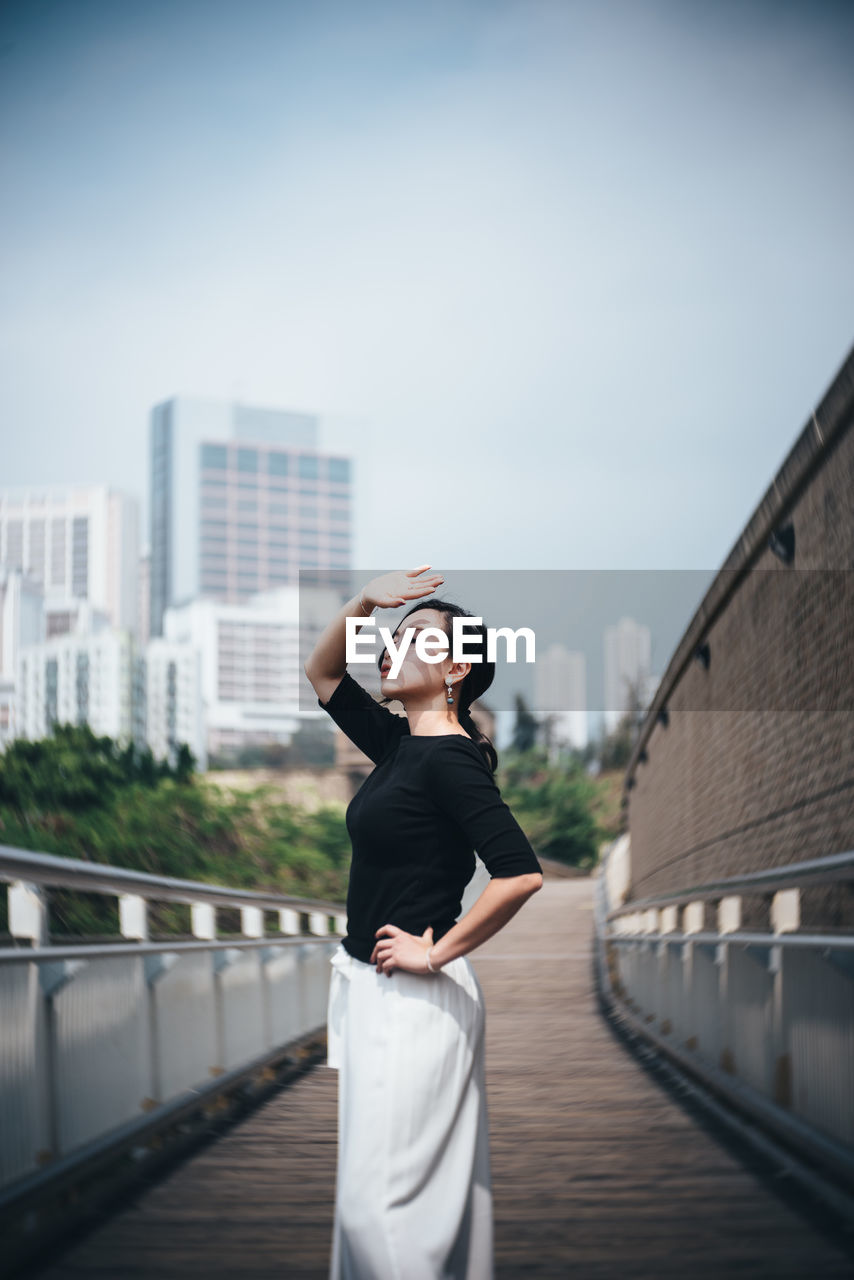 Woman Shielding Eyes While Standing Against Sky