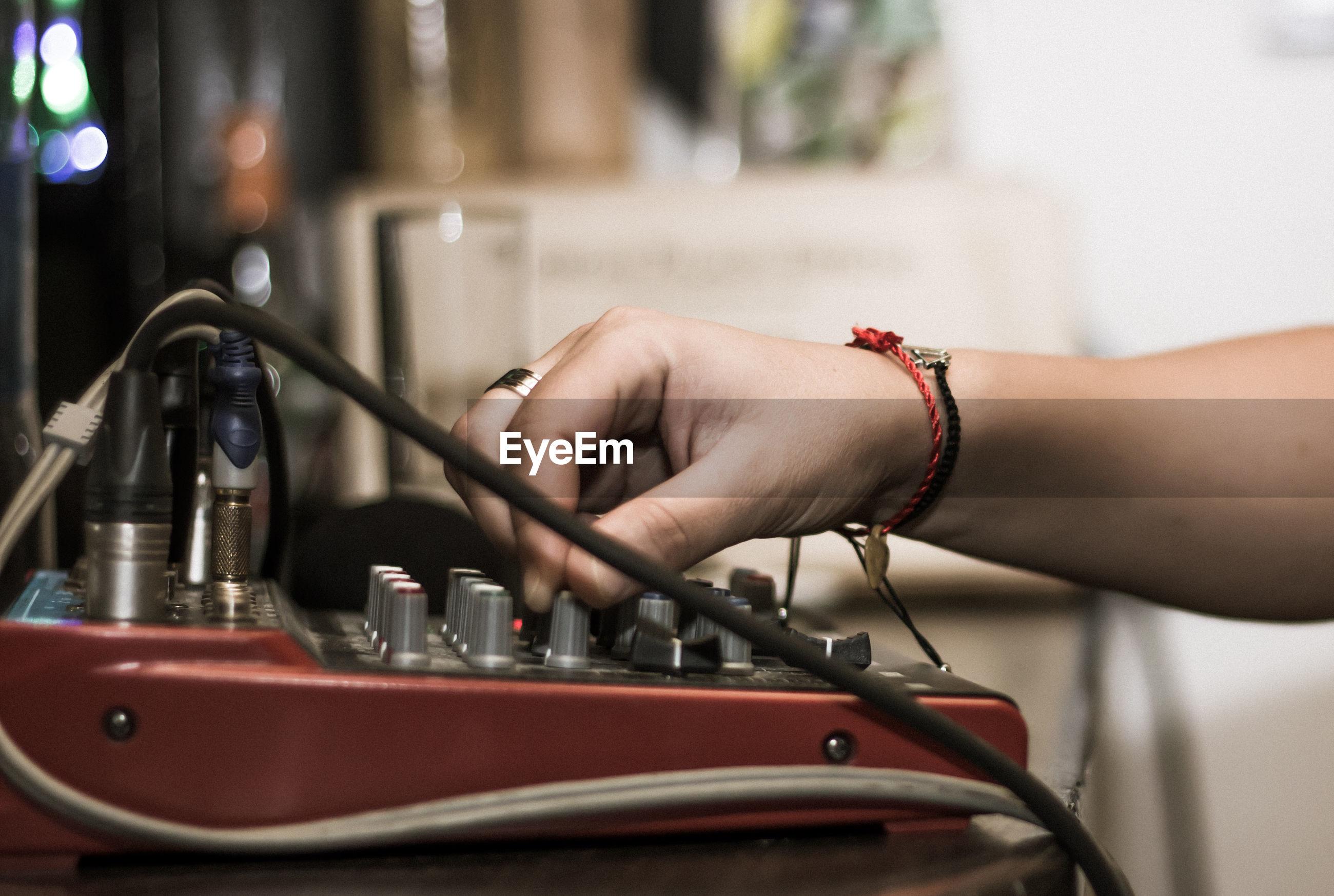 Cropped hand adjusting sound mixer knob