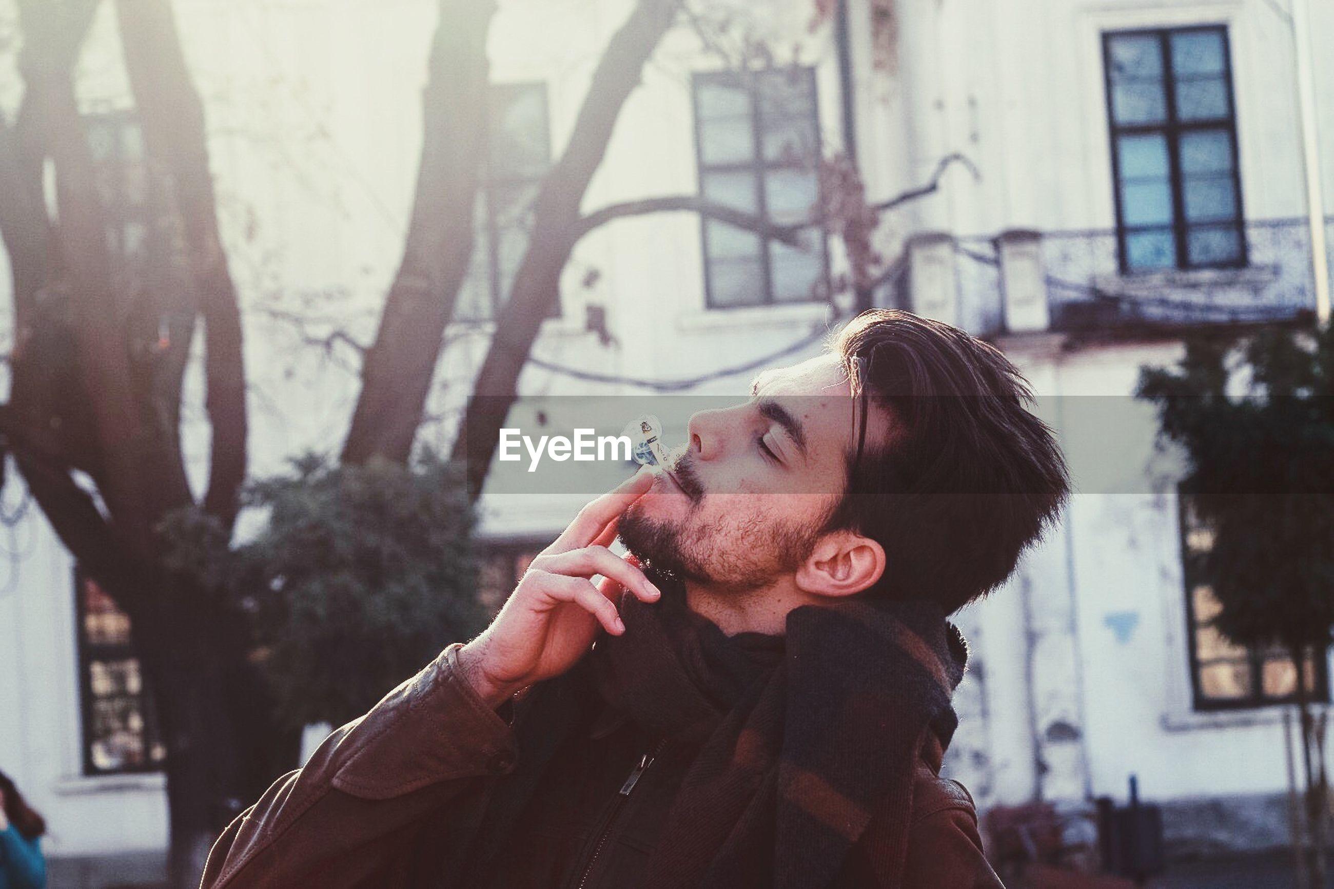 Young man smoking on city street