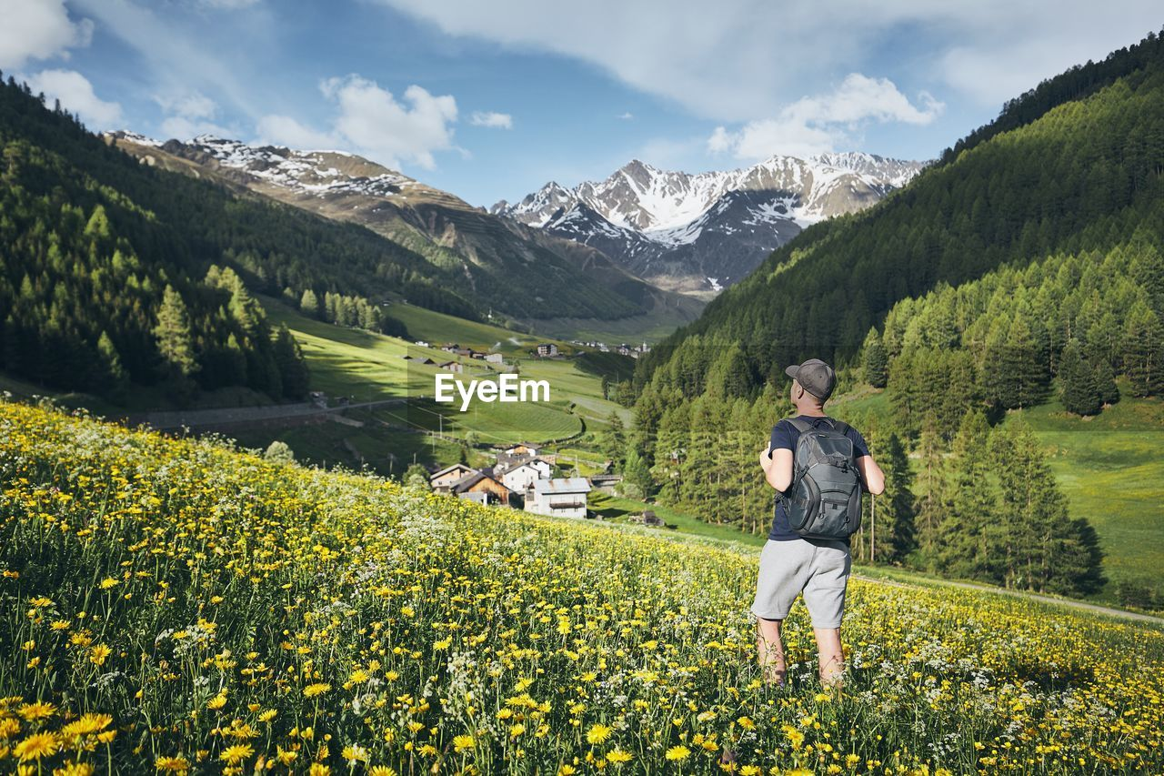 Rear View Of Man With Backpack Standing Amidst Flowering Plants On Field Against Mountains