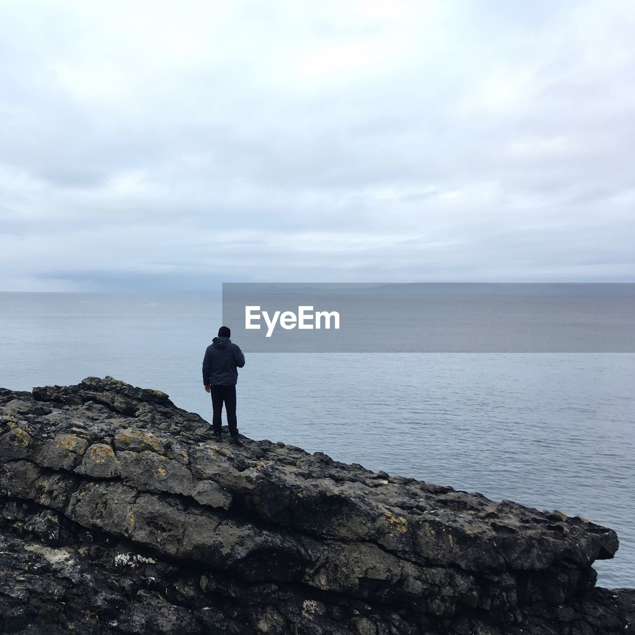 sea, sky, rock, water, standing, solid, rock - object, cloud - sky, real people, beauty in nature, leisure activity, scenics - nature, one person, horizon over water, lifestyles, horizon, full length, day, nature, outdoors, looking at view