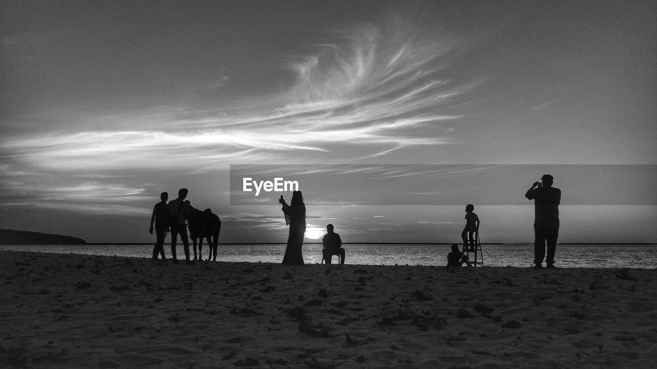 beach, land, sky, sea, group of people, water, horizon over water, horizon, real people, cloud - sky, beauty in nature, silhouette, nature, scenics - nature, sand, leisure activity, sunset, men, medium group of people, outdoors