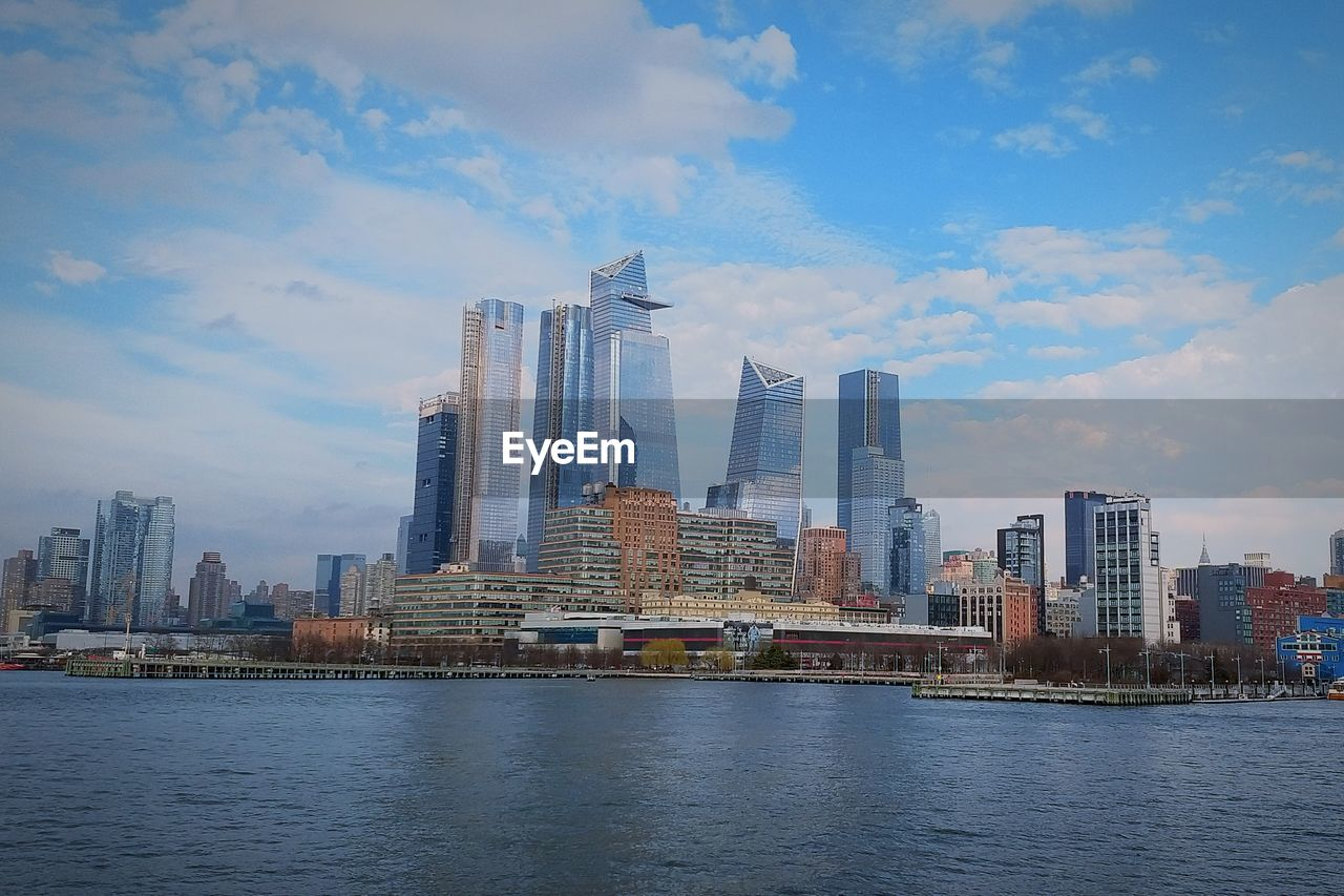 architecture, built structure, building exterior, sky, building, city, water, waterfront, cloud - sky, office building exterior, skyscraper, tall - high, urban skyline, landscape, nature, modern, office, no people, travel destinations, cityscape, outdoors, financial district, spire