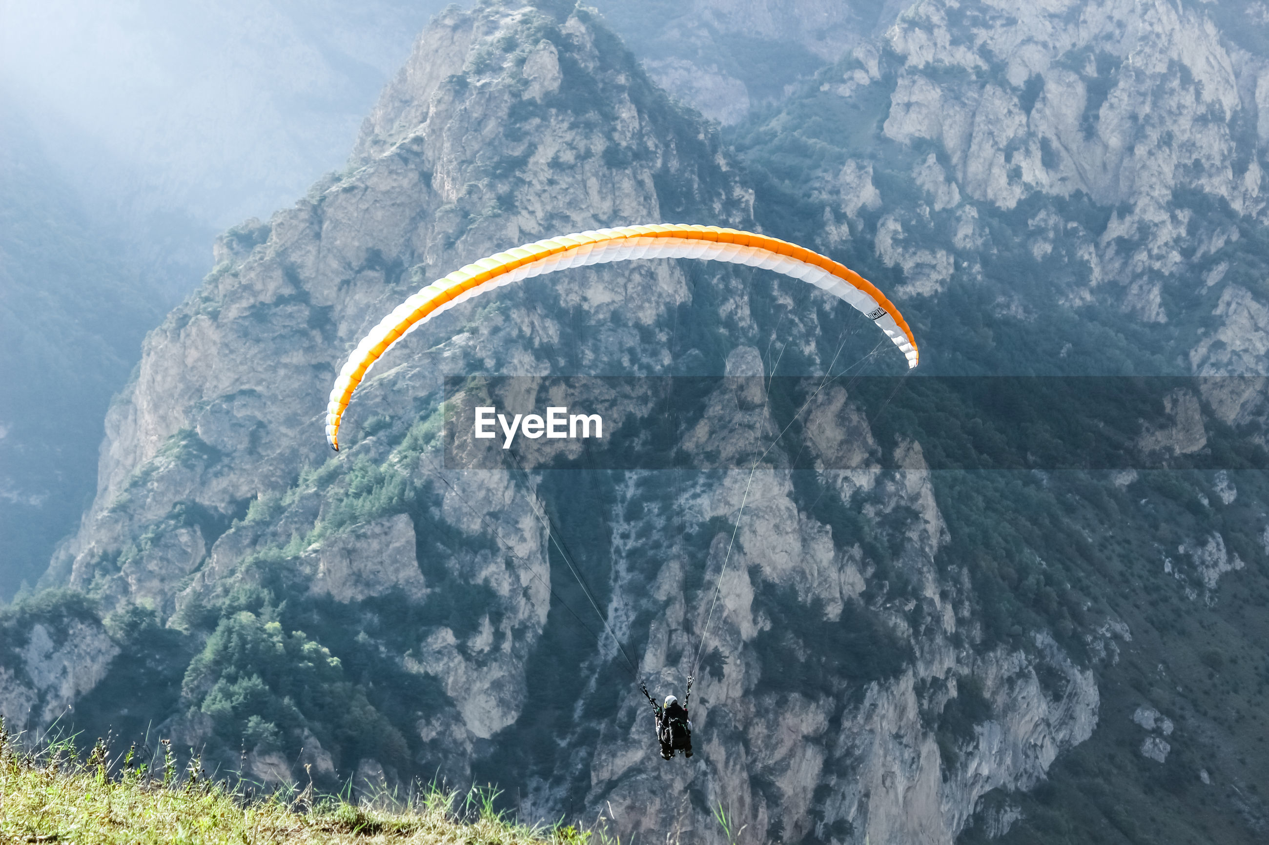 Man paragliding on mountain peak